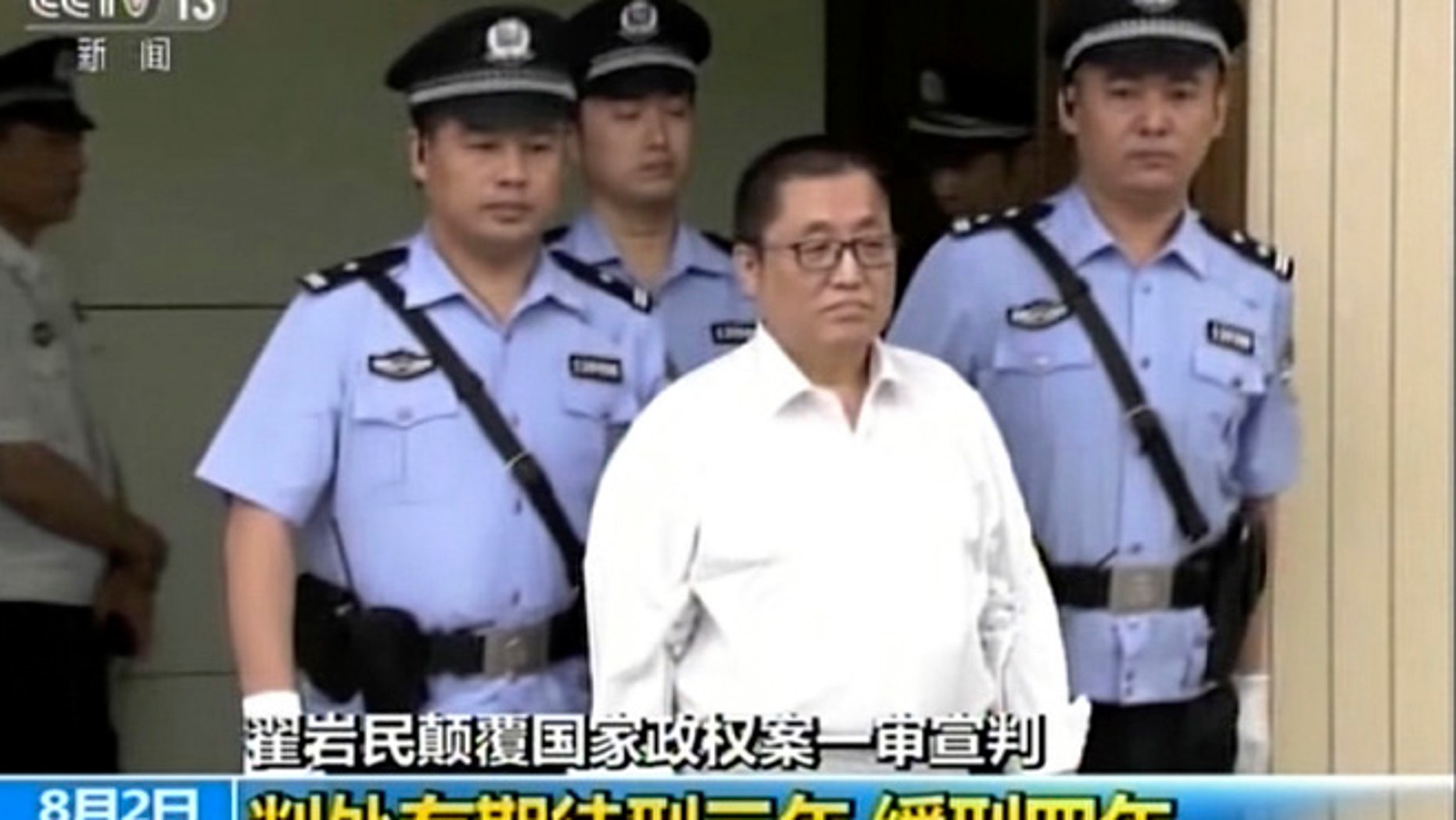 Aug. 2: China's CCTV and made available via AP Video, Zhai Yanmin wears a white shirt is escorted by policemen as he arrives the Tianjin No. 2 Intermediate People's Court in northern China's Tianjin Municipality.