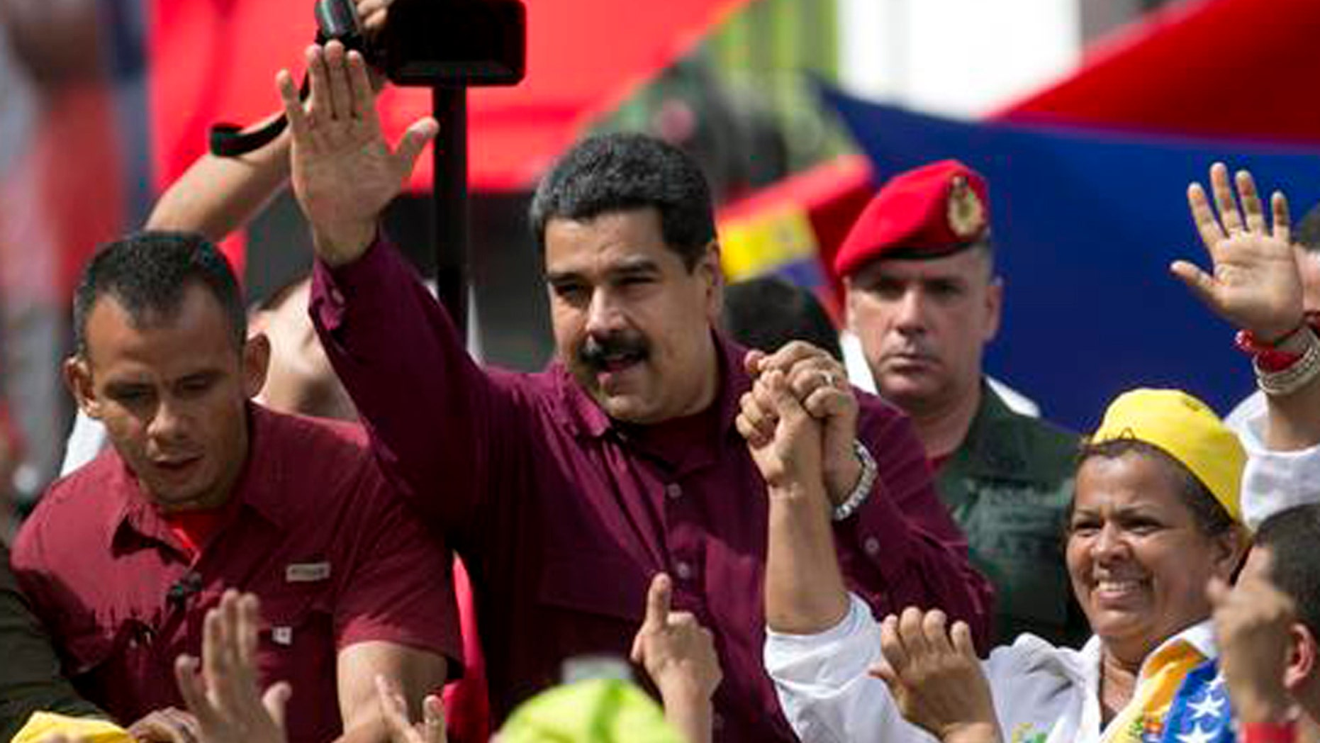 Venezuela's President Nicolas Maduro waves to supporters during a rally outside Miraflores presidential palace in Caracas, Venezuela, Friday, Oct. 28, 2016.