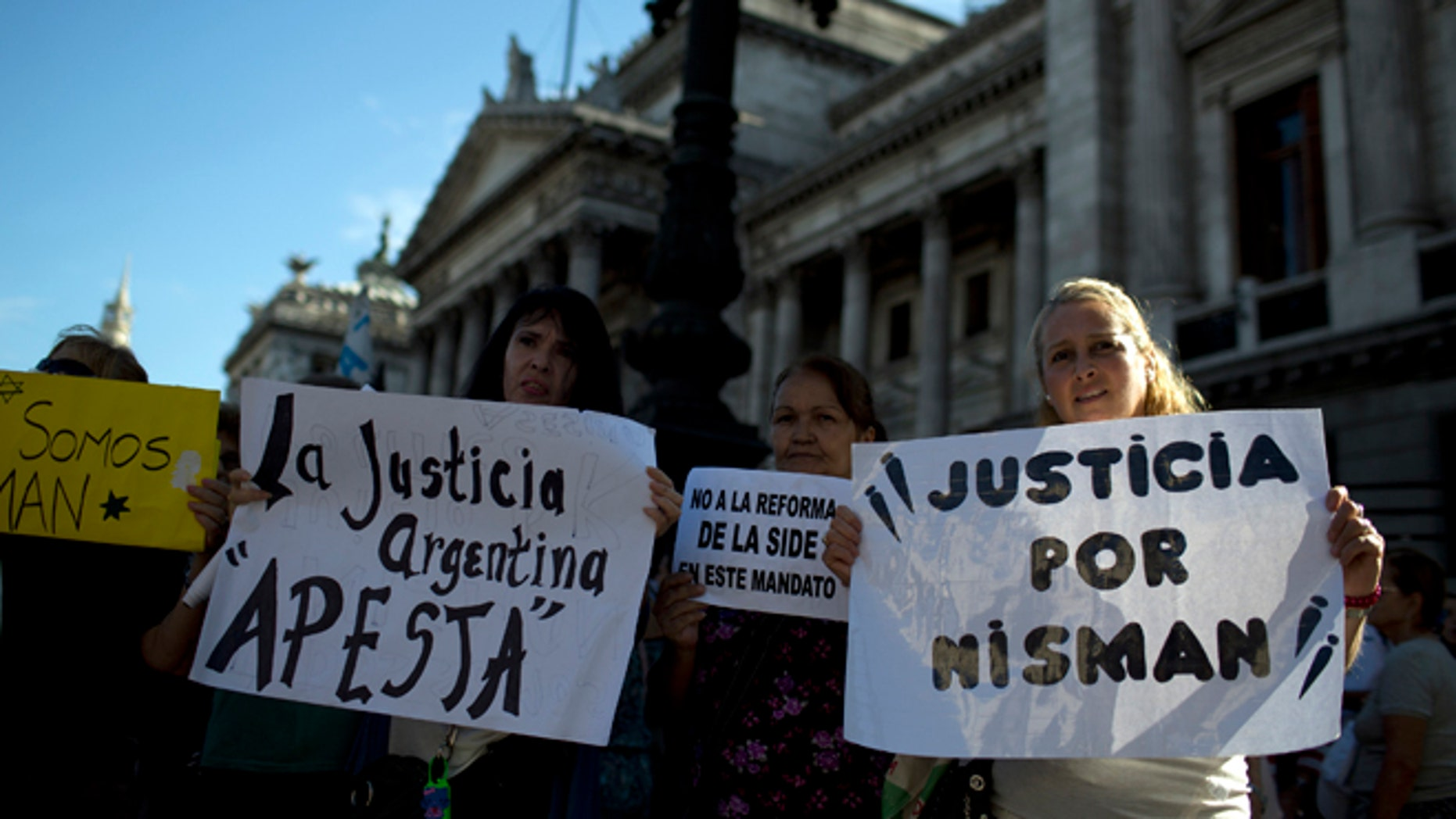 """Women holds sign that reads in Spanish; """"Argentine justice stinks,"""" second left, """"and """"Justice for Nisman,"""" right, during a march for justice and against impunity in the case of the mysterious death of late prosecutor Alberto Nisman, in Buenos Aires, Argentina, Wednesday, Feb. 4, 2015.  Investigators examining the death of Nisman, who accused Argentine President Cristina Fernandez of agreeing to shield the alleged masterminds of a 1994 terror bombing, said Tuesday, they have found a draft document he wrote requesting her arrest. (AP Photo/Rodrigo Abd)"""