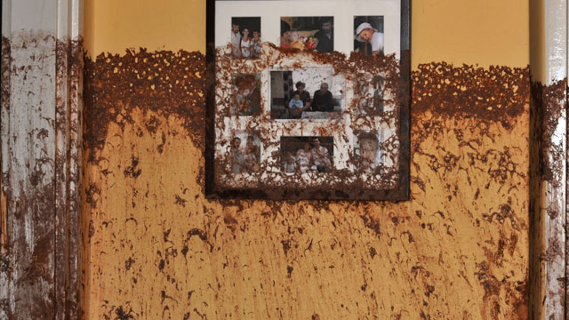 Family photos on a wall show the height of the sludge after a flood of toxic mud broke into a home in the village of Kolontar, Hungary, Thursday, Oct. 7, 2010. Monday's flooding was caused by the rupture of a red sludge reservoir at a metals works in western Hungary and has affected seven towns near the Ajkai, 100 miles (160 kilometers) southwest of Budapest. The flood of toxic mud killed a yet unknown number of people, injured more than one hundred, with some people still missing.