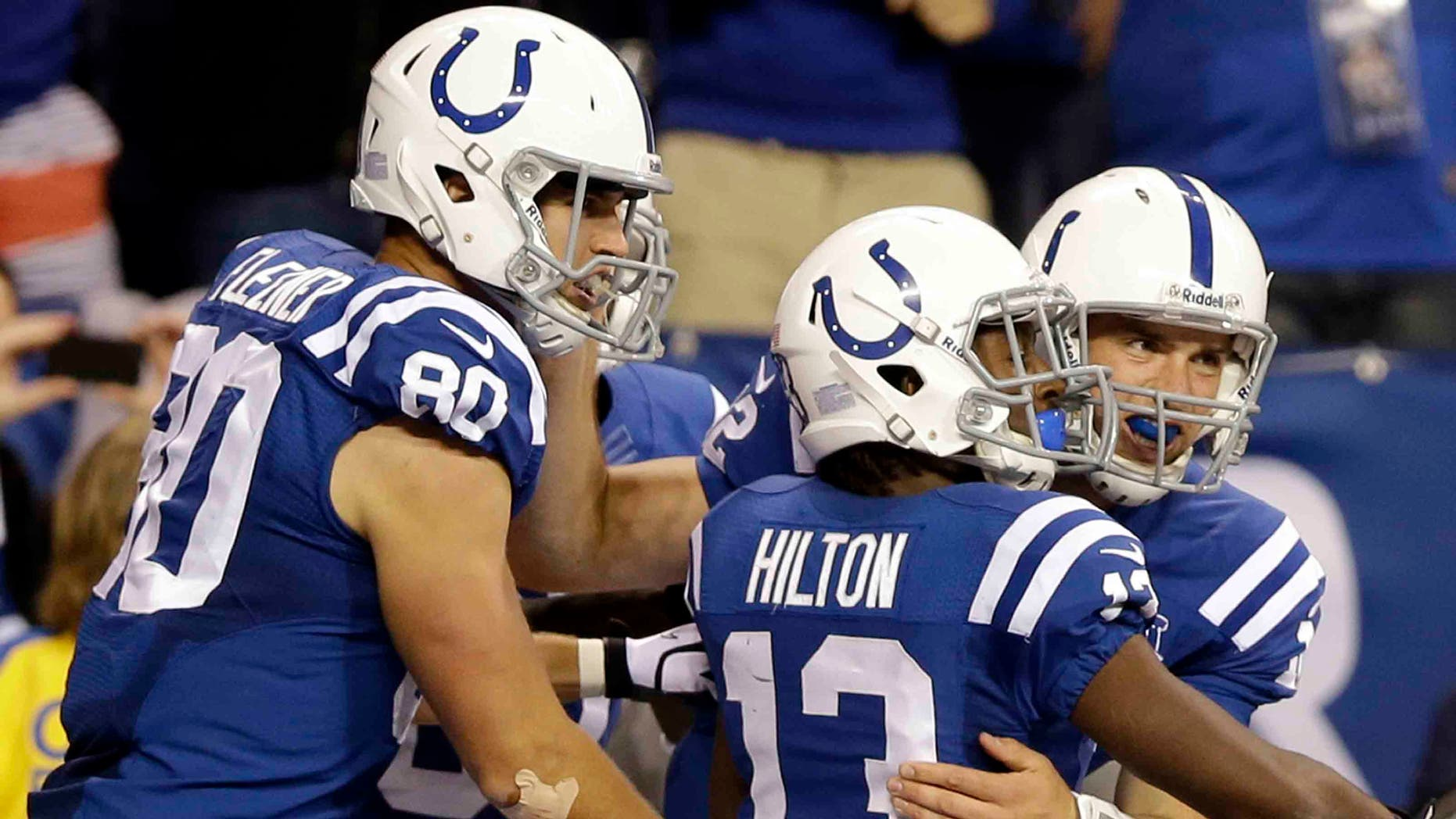 FILE - In this Oct. 20, 2013 file photo, Indianapolis Colts quarterback Andrew Luck celebrates his touchdown with tight end Coby Fleener (80) and wide receiver T.Y. Hilton (13) during the second half of an NFL football game against the Denver Broncos, in Indianapolis. Last season, the Colts overcame the loss of Peyton Manning and the loss of their coach as he battled cancer to make the playoffs. This season, Andrew Luck has already guided Indy to three fourth-quarter wins and the Colts are a remarkable 13-2 in one-possession games over the last two seasons.(AP Photo/Michael Conroy, File)