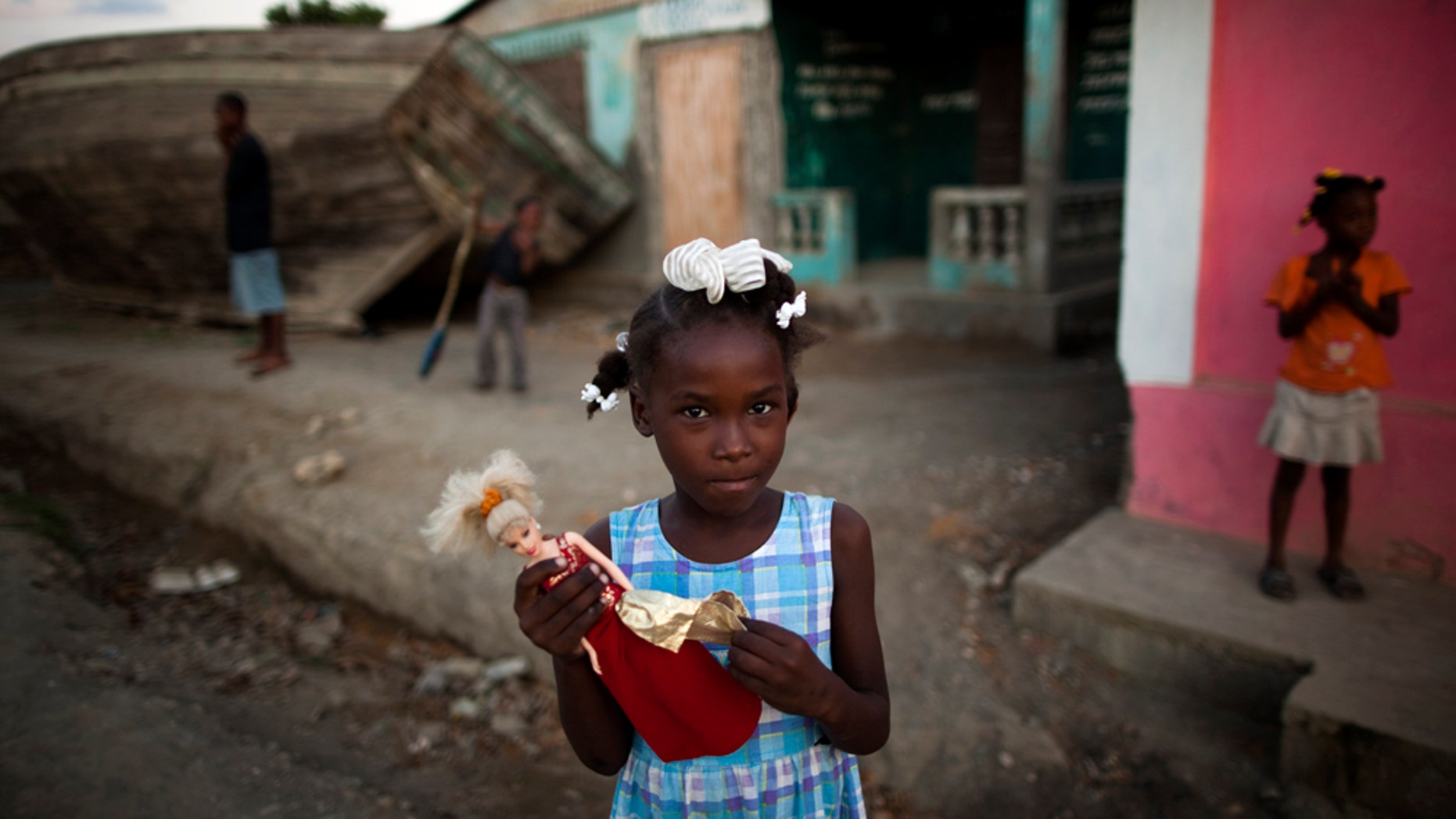 Claudine holds a Barbie doll next to the port in Port-du-Paix, Haiti, Thursday, Jan. 27, 2011. (AP Photo/Rodrigo Abd)