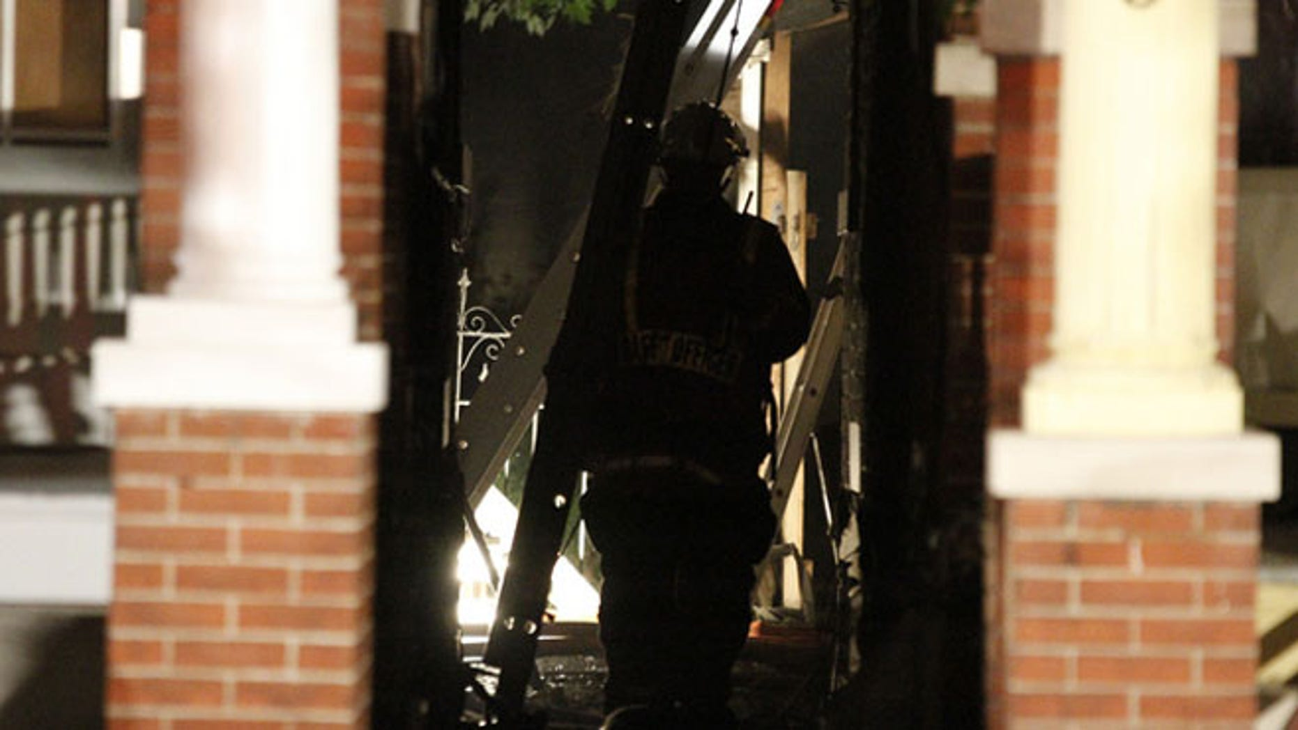 July 4: Firefighters inspect a home where four people died in an early morning fire.