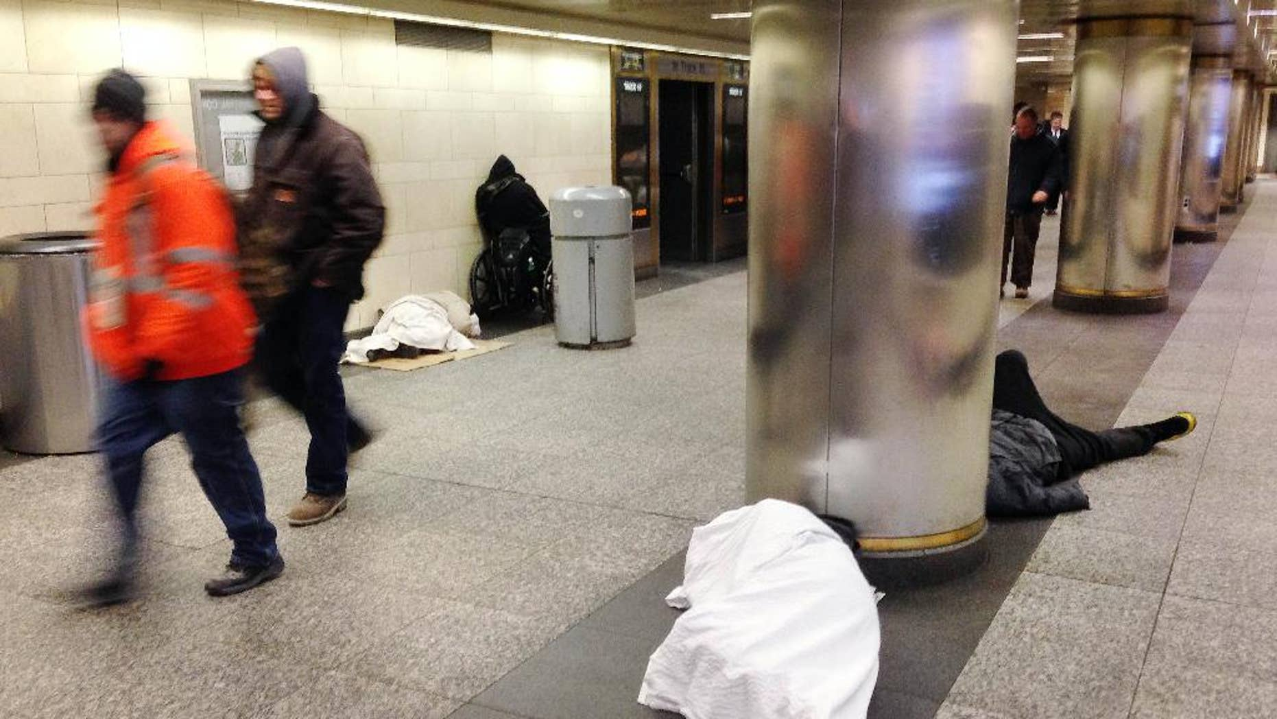 Jan. 8, 2015: Homeless people, seeking shelter from the cold, sleep on the floor of New York's Penn Station as commuters walk past. (AP)