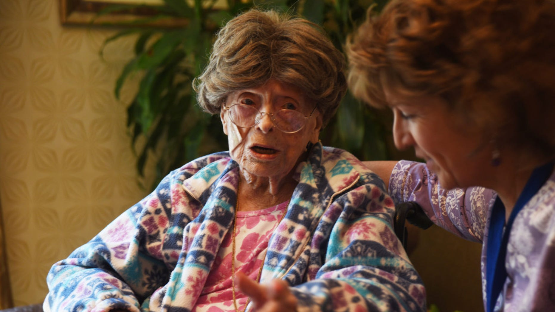 Adele Dunlap, 113, talks to a caregiver in Pittstown, N.J.