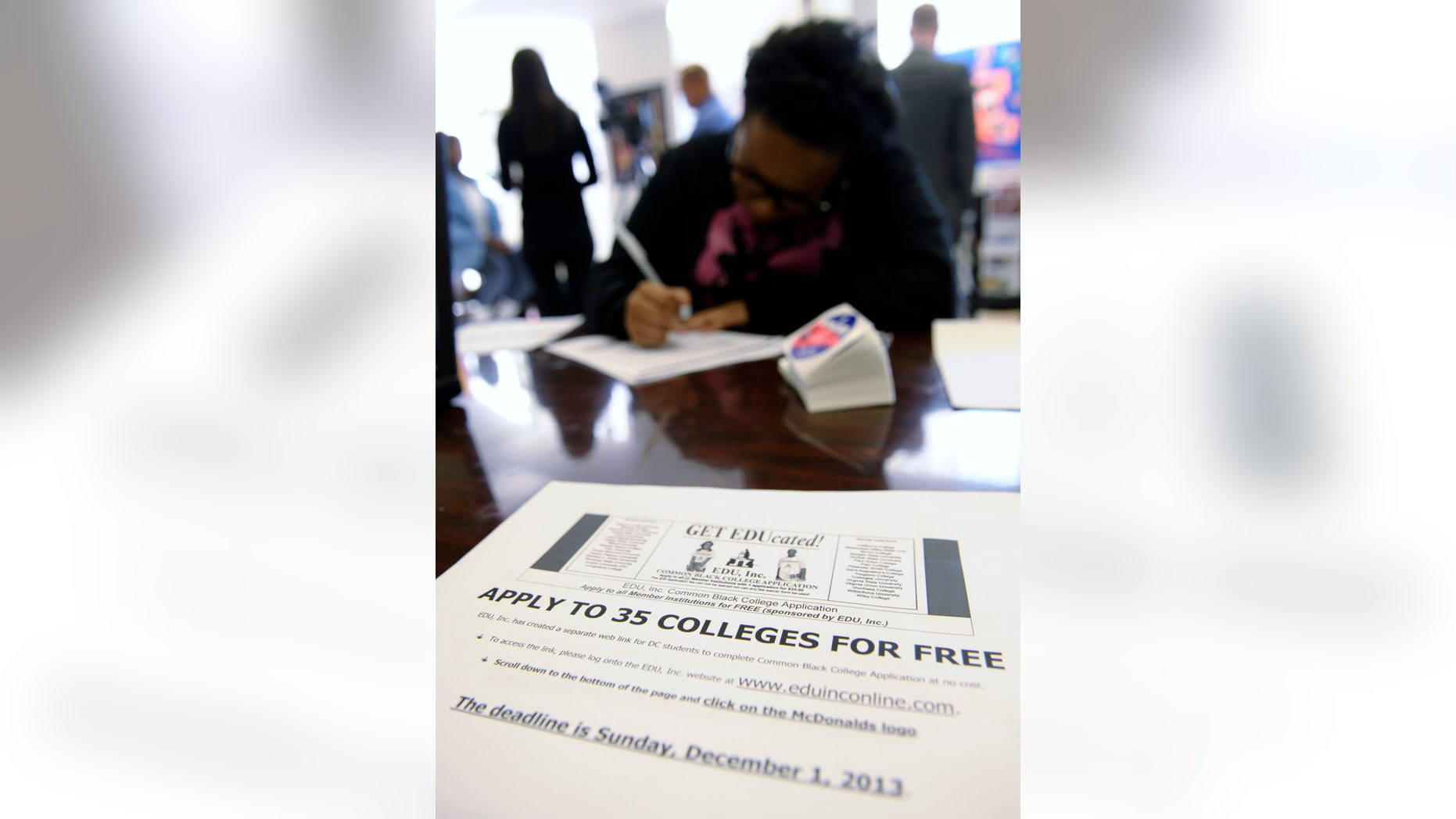 """Scheryl Duarte, a senior at Roosevelt High School, fills out a college enrollment application at her school in Washington, Nov. 14, 2013. The schools was hosting a """"sit-in"""" to get high school students who might not otherwise go to college to apply to college. President Barack Obama's goal is that by 2020, America will again have the highest proportion of college graduates in the world. More low-income and first-generation students must get a degree to reach it. The first hurdle is getting these students to apply. (AP Photo/Susan Walsh)"""