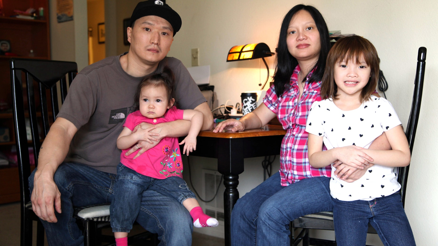 March 19, 2015: Korean adoptee Adam Crapser, left, poses with daughters, Christal, 1, Christina, 5, and his wife, Anh Nguyen, in the family's living room in Vancouver, Wash.