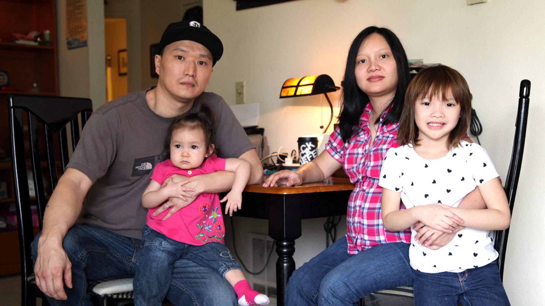 In this March 19, 2015, file photo, Korean adoptee Adam Crapser, left, poses with daughters, Christal and Christina and his wife, Anh Nguyen, in the family's living room in Vancouver, Wash.