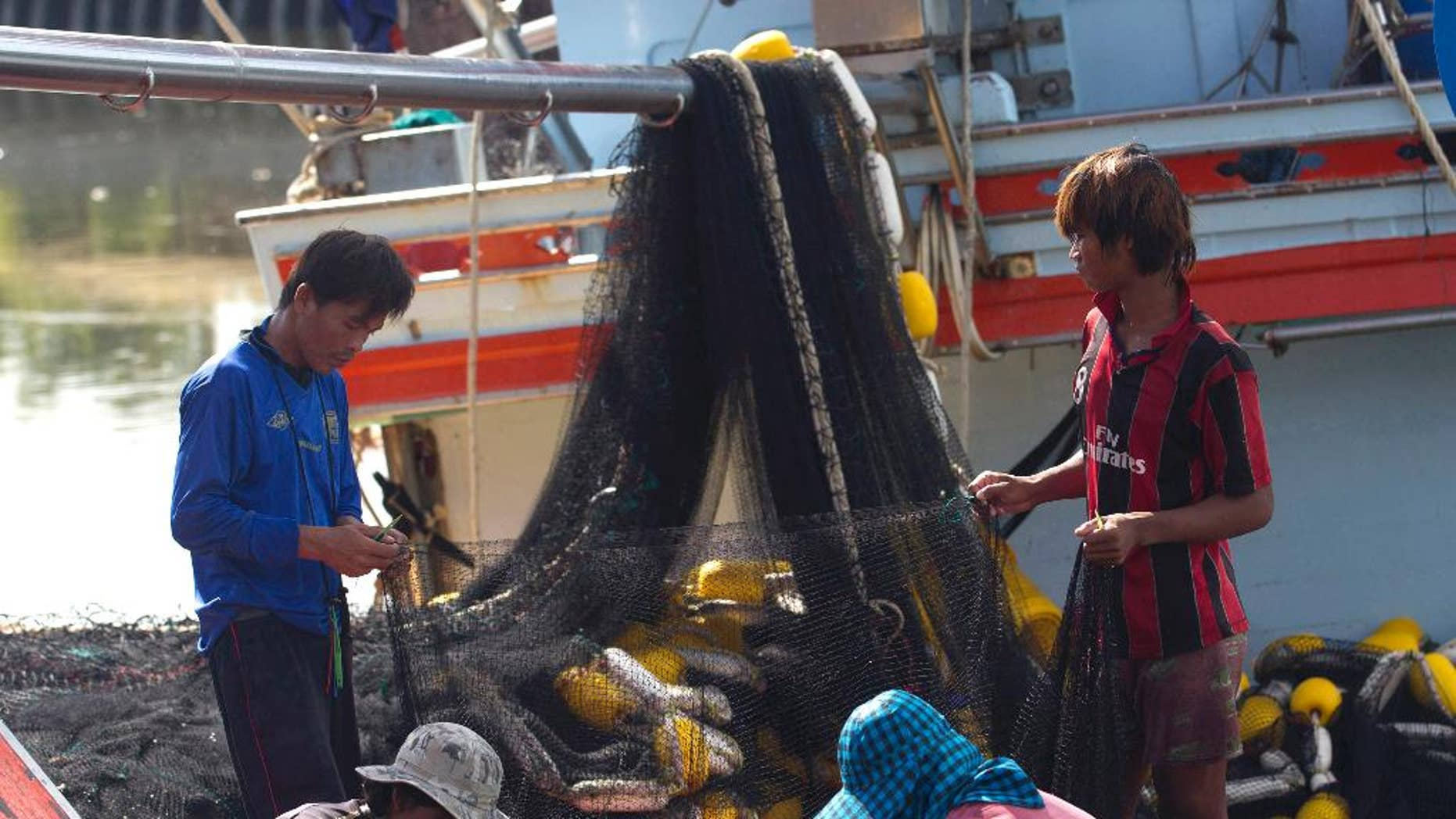 """FILE - In this Sept. 3, 2013 file photo, migrant workers from Myanmar clean fishing nets aboard a trawler after a fishing trip in the Gulf of Thailand in Samut Sakhon Province, west of Bangkok, Thailand. The European Union says Thailand must take """"swift and determined action"""" by next month to improve its fisheries and labor practices or the threat of a seafood ban will come closer.(AP Photo/Sakchai Lalit, File)"""