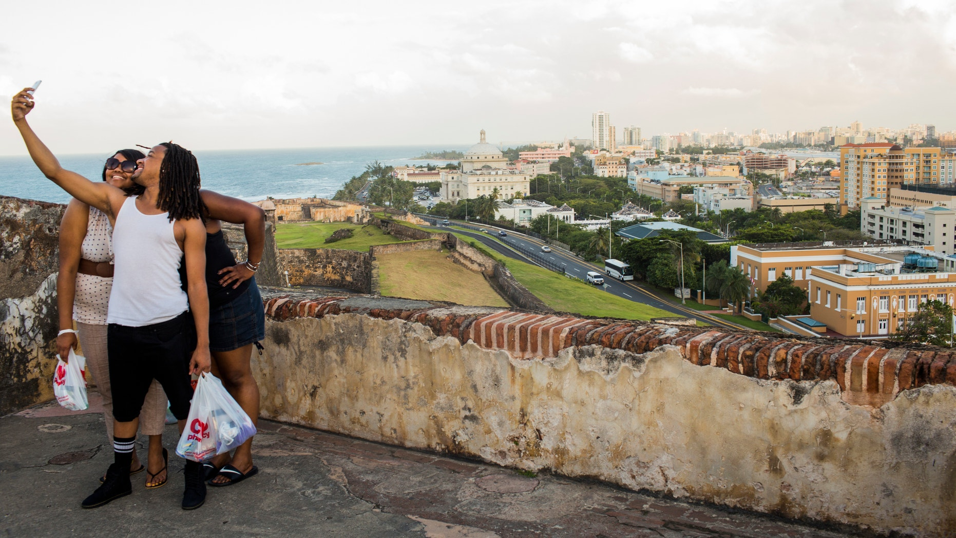 Friends pose for a photo in front of Old San Juan, the center for Puerto Rican tourism, on November 12, 2013.