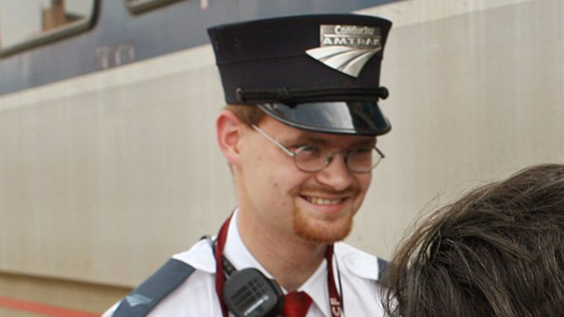 In this Aug. 21, 2007 photo, Amtrak assistant conductor, Brandon Bostian stands by as passengers board a train.