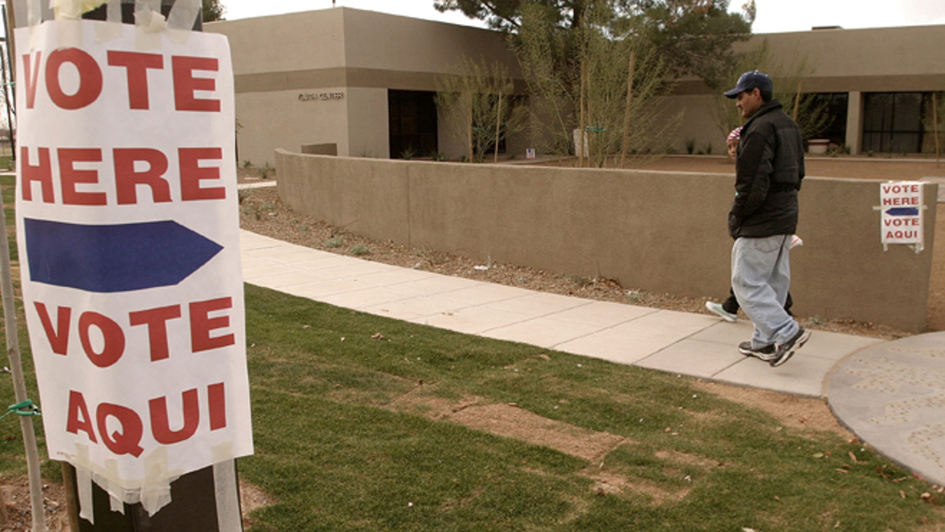 Lupe Montoya (wearing cap) and his neighbor Juana Nicholas, of El Mirage, Arizona walk to the El Mirage Youth Center, February 3, 2004 where they will vote in the state's democratic presidential primary election. (Photo by Jeff Topping/Getty Images)
