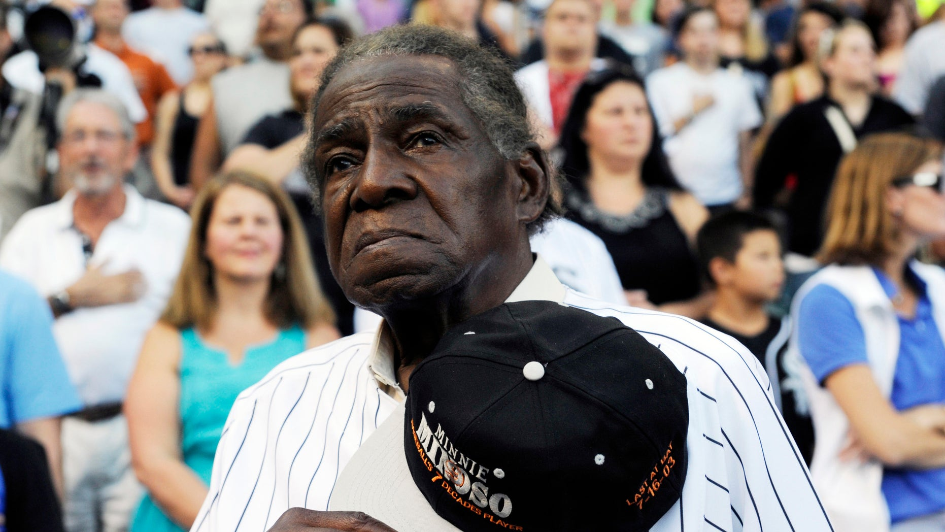 FILE - In a Aug. 24, 2013 file photo, former Negro Leaguer and Chicago White Sox player Minnie Minoso stands during the national anthem before a baseball game between the Chicago White Sox and the Texas Rangers, in Chicago.  Major league baseball's first black player in Chicago, Minnie Minoso, has died. The Cook County medical examiner confirmed his death Sunday, March 1, 2015. There is some question about his age but the White Sox say he was 92. (AP Photo/David Banks, File)