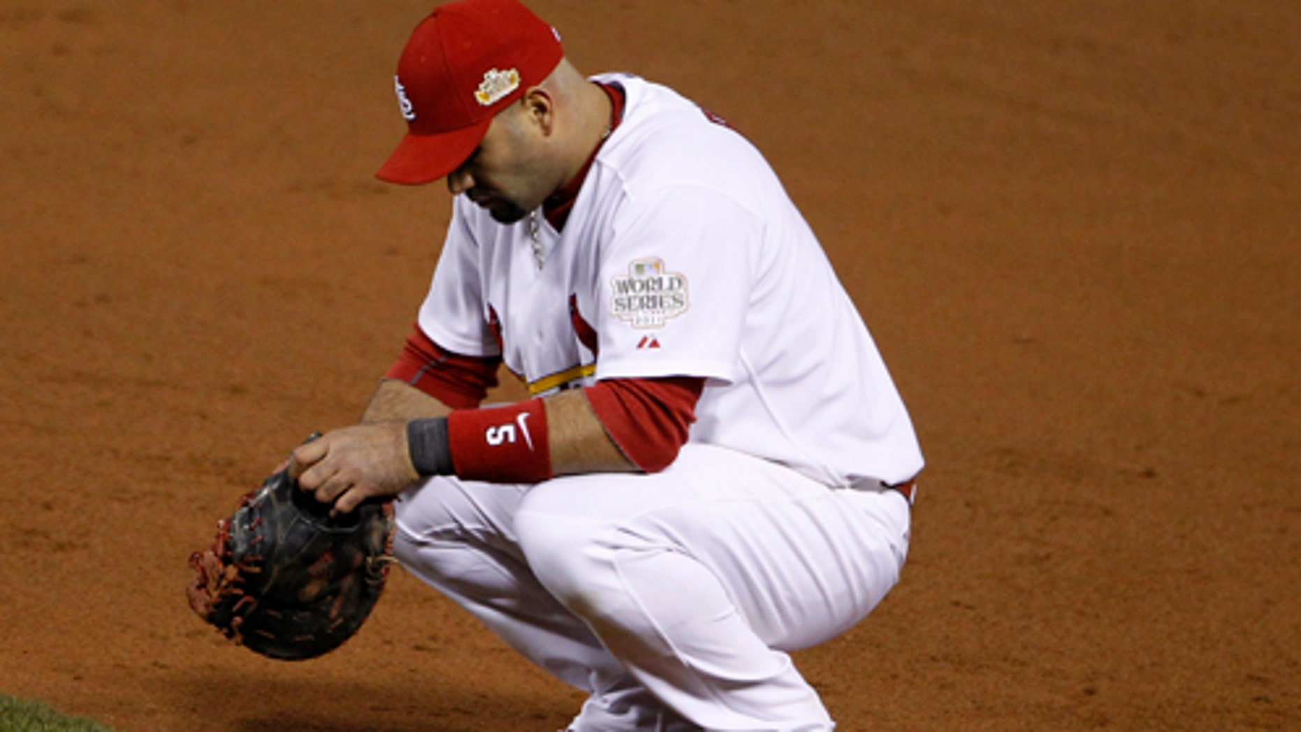 St. Louis Cardinals' Albert Pujols pauses during a pitching change during the ninth inning of Game 2 of baseball's World Series against the Texas Rangers Thursday, Oct. 20, 2011, in St. Louis. (AP Photo/Eric Gay)