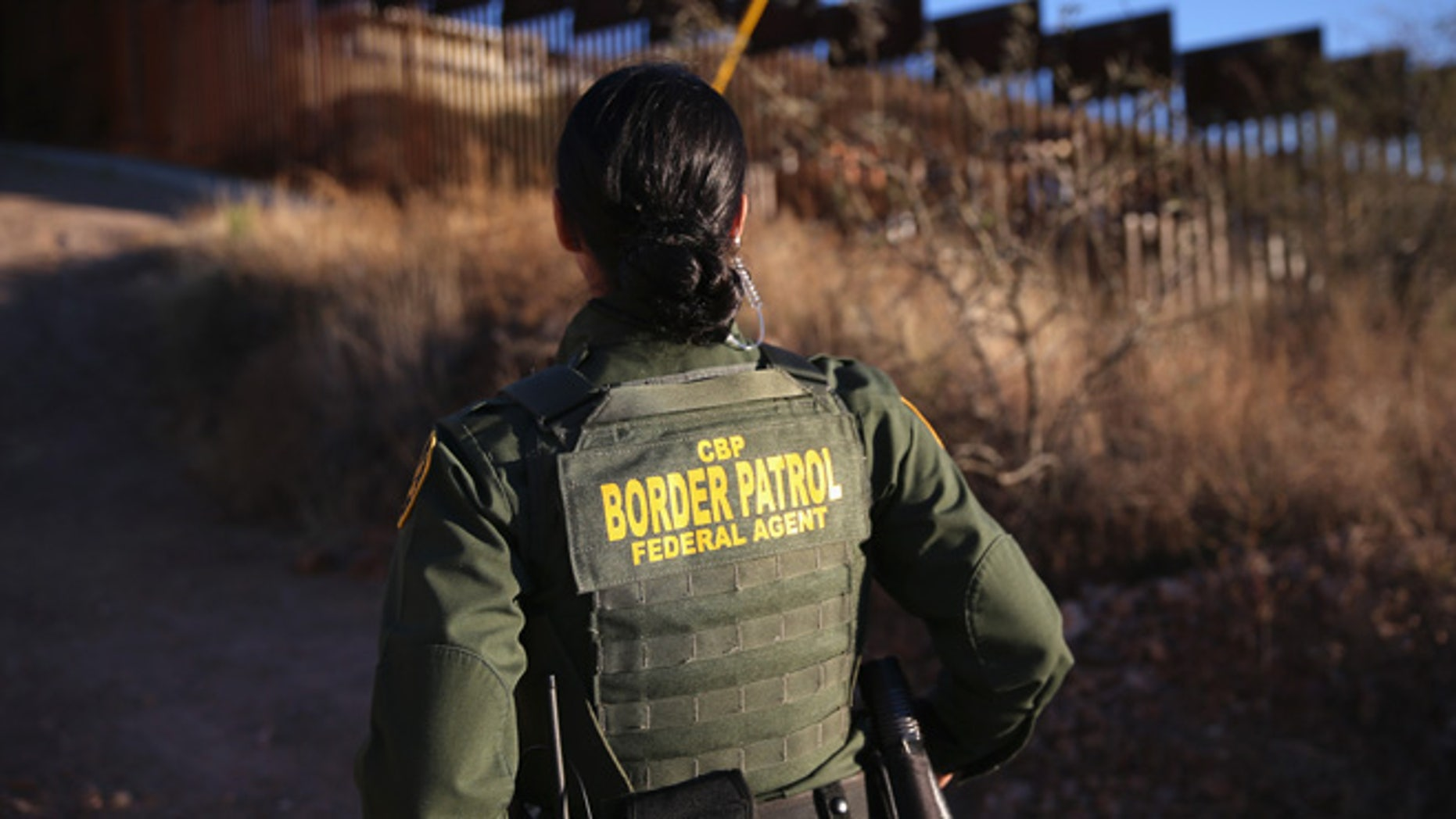 NOGALES, AZ - DECEMBER 09:  U.S. Border Patrol agent Nicole Ballistrea watches over the U.S.-Mexico border fence on December 9, 2014 in Nogales, Arizona. (Photo by John Moore/Getty Images)