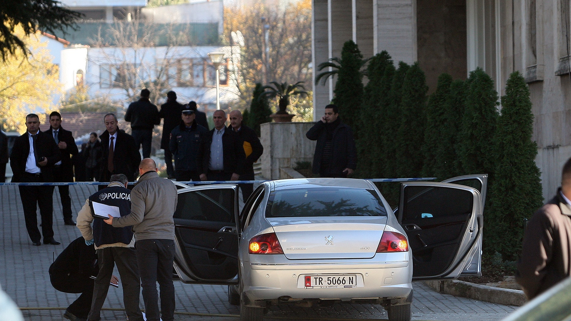 Police and officials inspect the car of Besnik Dervishi, a prefect, senior executive official of a southwestern district, in which police found 200 grams of C4 explosive, two detonators and a cell phone while entering the government's main building in capital Tirana Friday, Dec. 13, 2013.(AP Photo/Hektor Pustina)