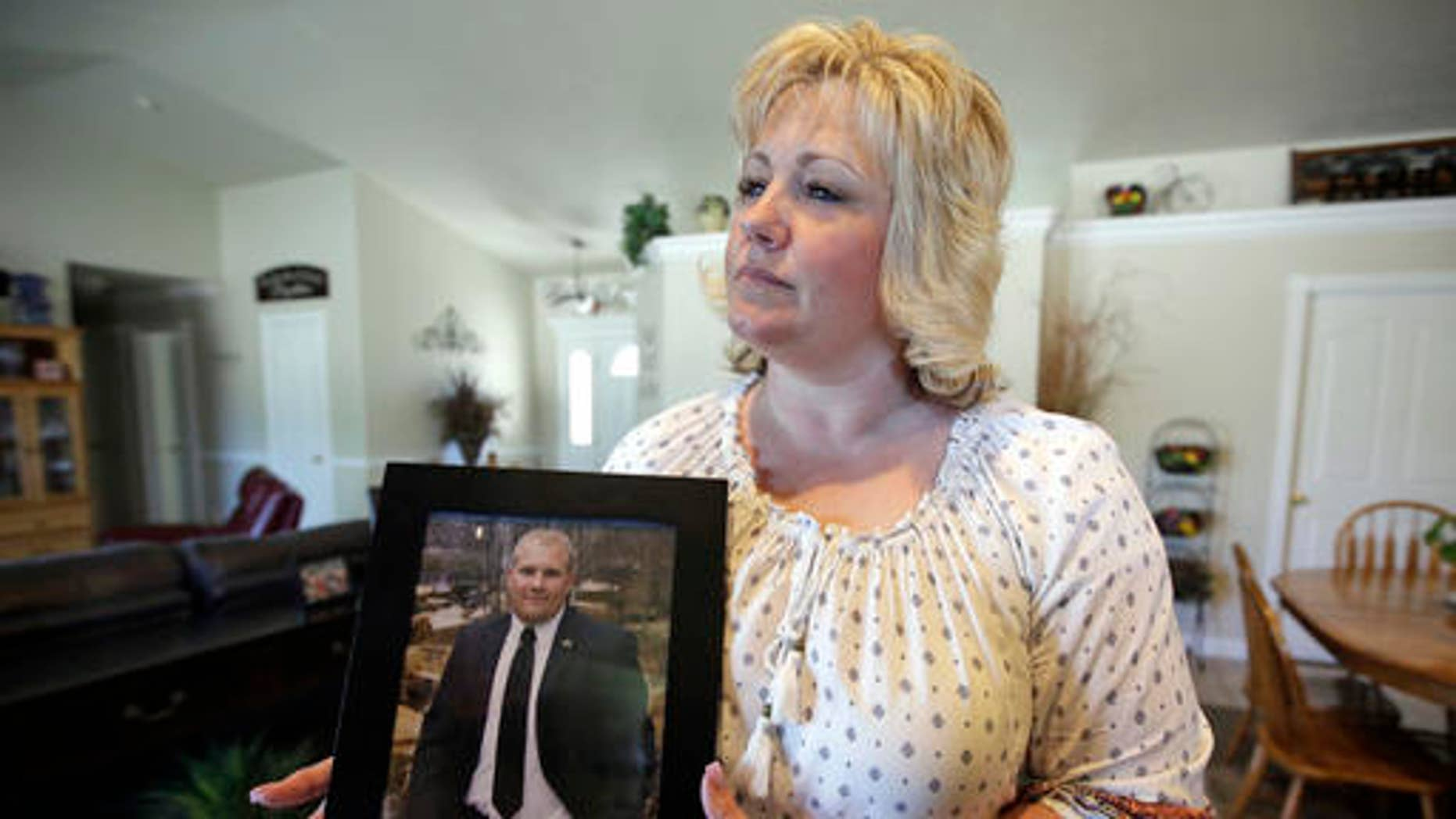 FILE - In this July 13, 2016 file photo, Laurie Holt holds a photograph of her son Josh Holt at her home, in Riverton, Utah. U.S. government officials and Holt, the mother of a Utah man jailed in Venezuela are worried about his deteriorating health. Josh Holt has been jailed since June 30 on suspicion of weapons charges. He traveled to Venezuela to marry a fellow Mormon he met online. His mother says he's innocent.  (AP Photo/Rick Bowmer, File)