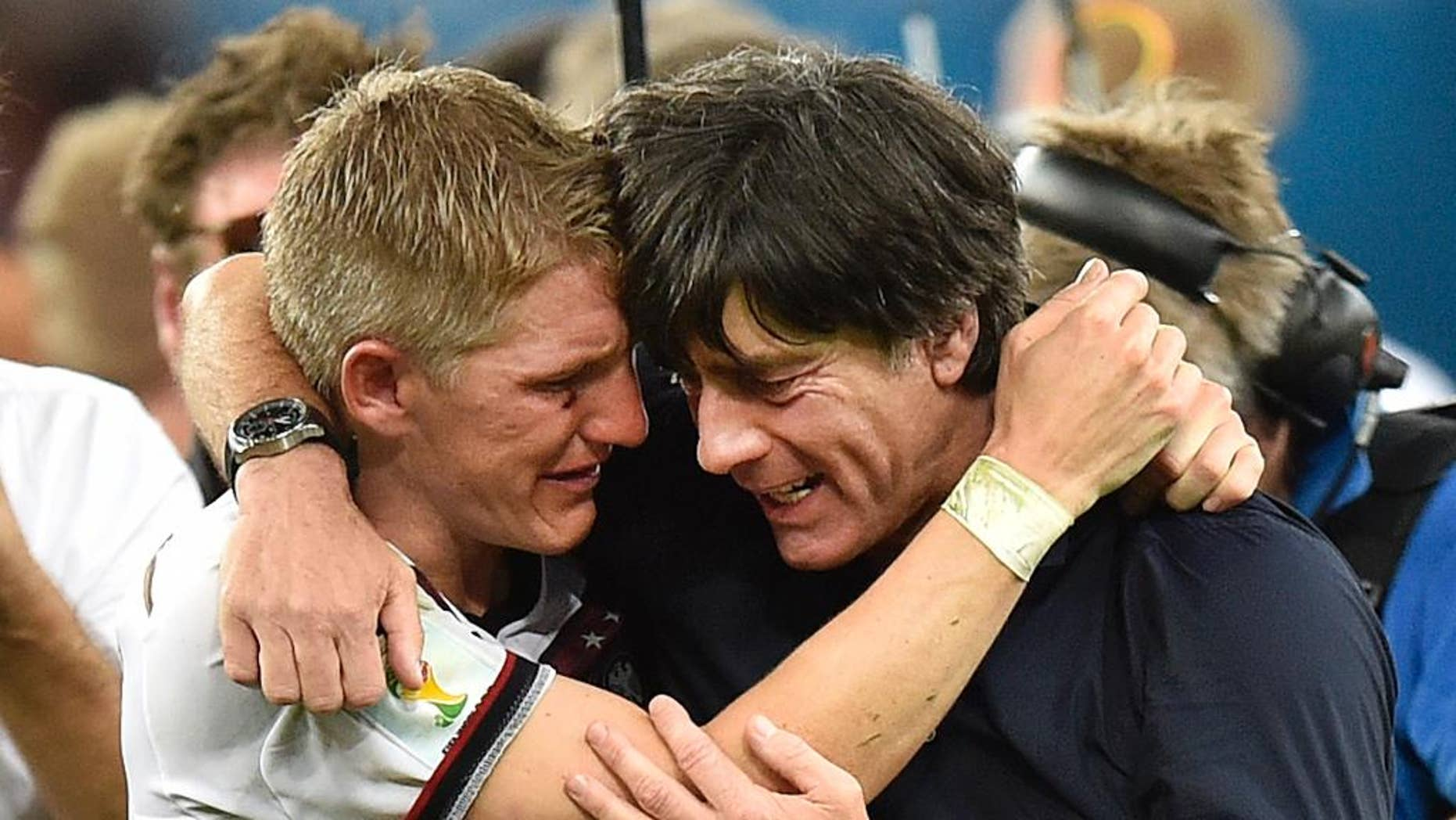 Germany's Bastian Schweinsteiger and Germany's head coach Joachim Loew embrace after the World Cup final soccer match between Germany and Argentina at the Maracana Stadium in Rio de Janeiro, Brazil, Sunday, July 13, 2014. Germany won the match 1-0 (AP Photo/Martin Meissner)