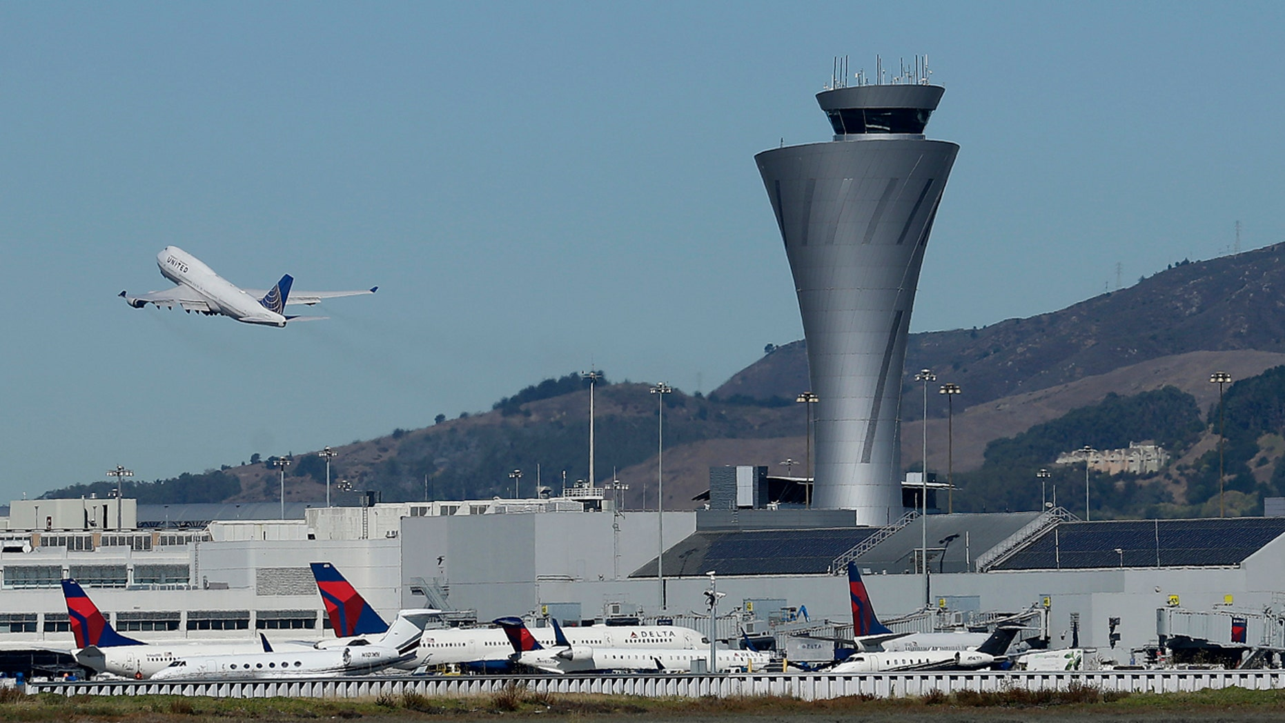 In this Oct. 24, 2017, file photo, the air traffic control tower is in sight as a plane takes off from San Francisco International Airport in San Francisco.