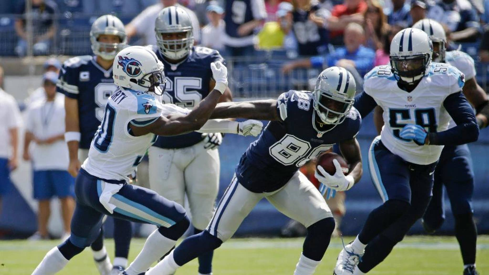 Dallas Cowboys wide receiver Dez Bryant (88) tries to get past Tennessee Titans cornerback Jason McCourty (30) in the first quarter of an NFL football game Sunday, Sept. 14, 2014, in Nashville, Tenn. (AP Photo/Wade Payne)