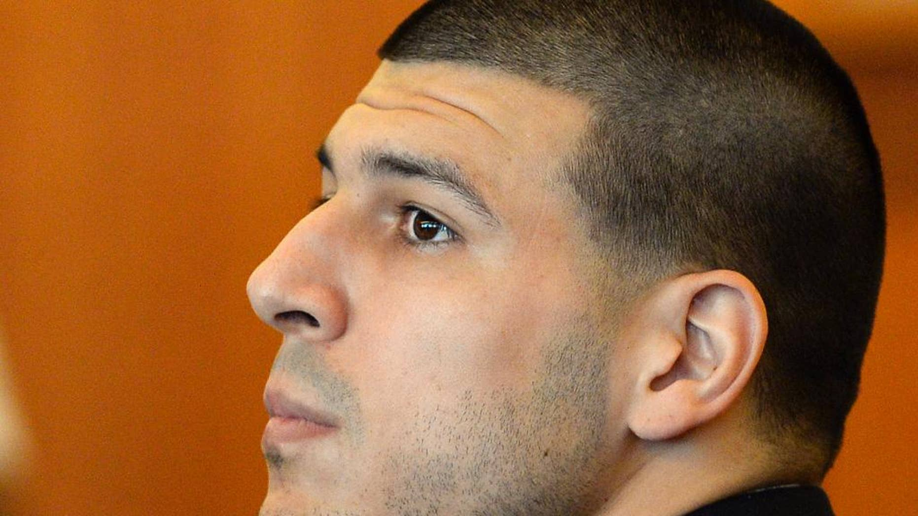 FILE - In this Tuesday, July 22, 2014, file photo, former NFL football player Aaron Hernandez watches during a hearing in Bristol County Superior Court, in Fall River, Mass. A judge is hearing arguments, Tuesday, Sept. 30, 2014, on a bid by Hernandez's lawyers to have additional evidence in a murder case against him thrown out. (AP Photo/CJ Gunther, Pool, File)