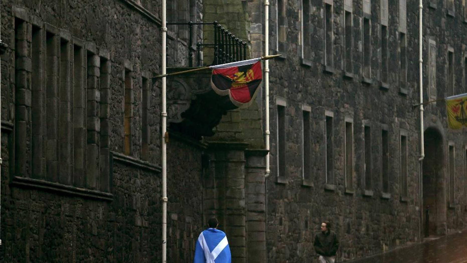 A man draped in a Saltire walks up the Royal Mile in Edinburgh, Scotland, Friday, Sept. 19, 2014. Scottish voters have rejected independence and decided that Scotland will remain part of the United Kingdom. The result announced early Friday was the one favored by Britain's political leaders, who had campaigned hard in recent weeks to convince Scottish voters to stay. It dashed many Scots' hopes of breaking free and building their own nation. (AP Photo/Scott Heppell)