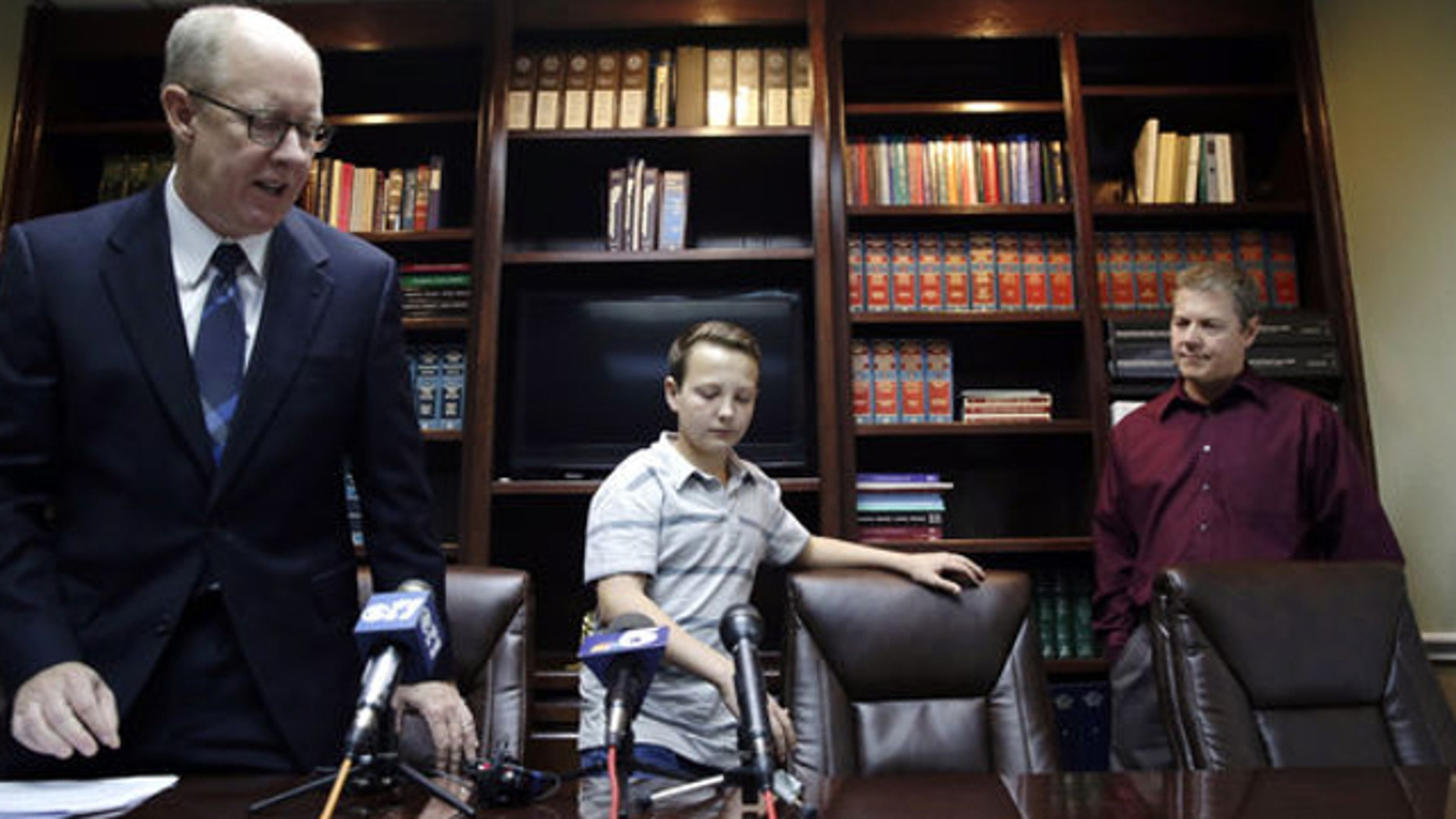 March 26, 2014: Lucas McConnell, 13, center, takes a seat before speaking to reporters with his attorney Todd Clement, left, and his father Kevin McConnell by his side in Burleson, Texas.