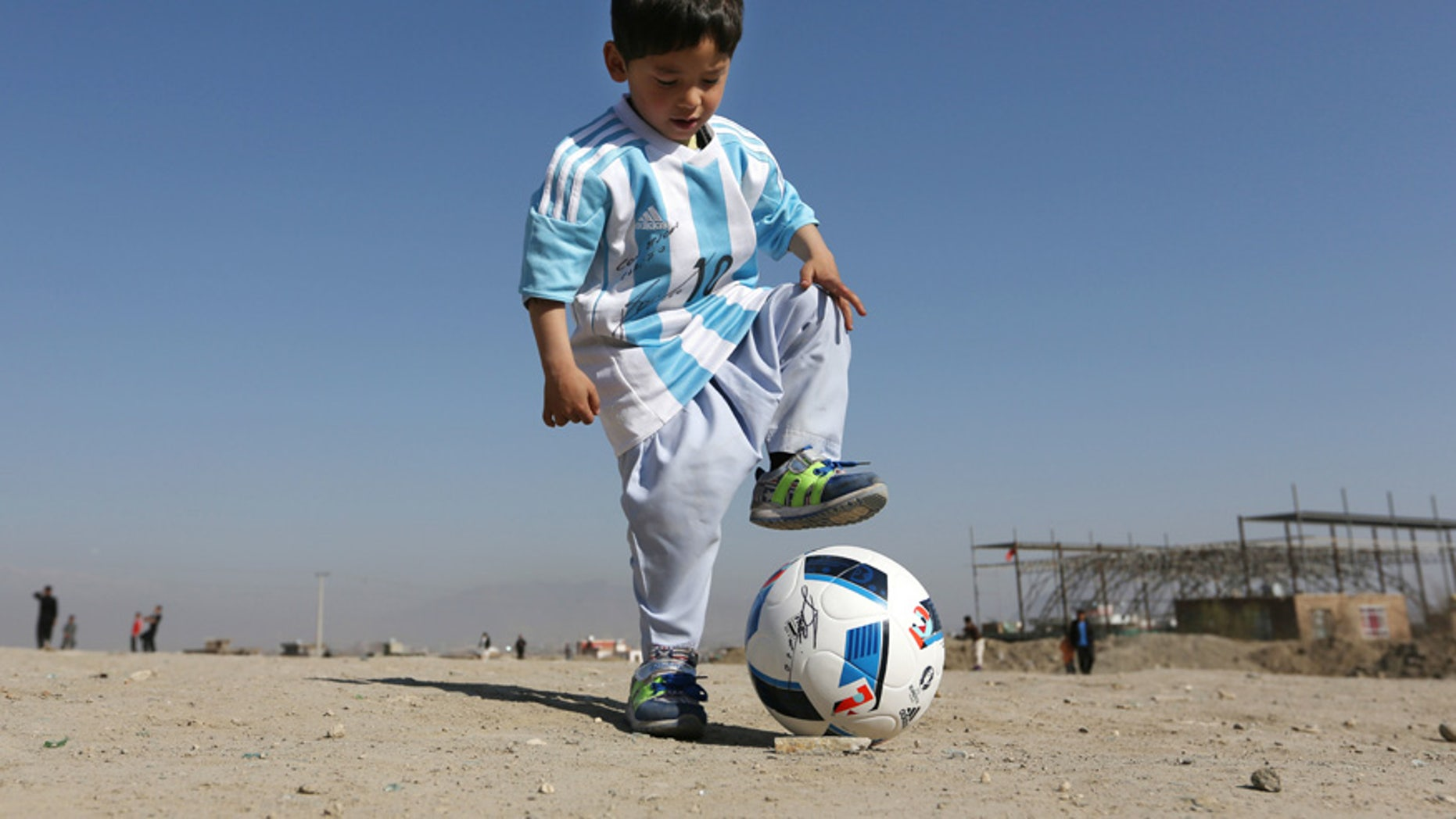 Feb. 26, 2016: Murtaza Ahmadi, a five-year-old Afghan Lionel Messi fan plays with a soccer ball during a photo opportunity as he wears a shirt signed by Messi, in Kabul, Afghanistan.