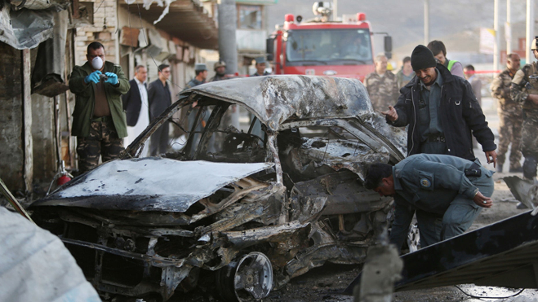April 10, 2015: Afghan security personnel gather at the site of a suicide attack in Kabul, Afghanistan.