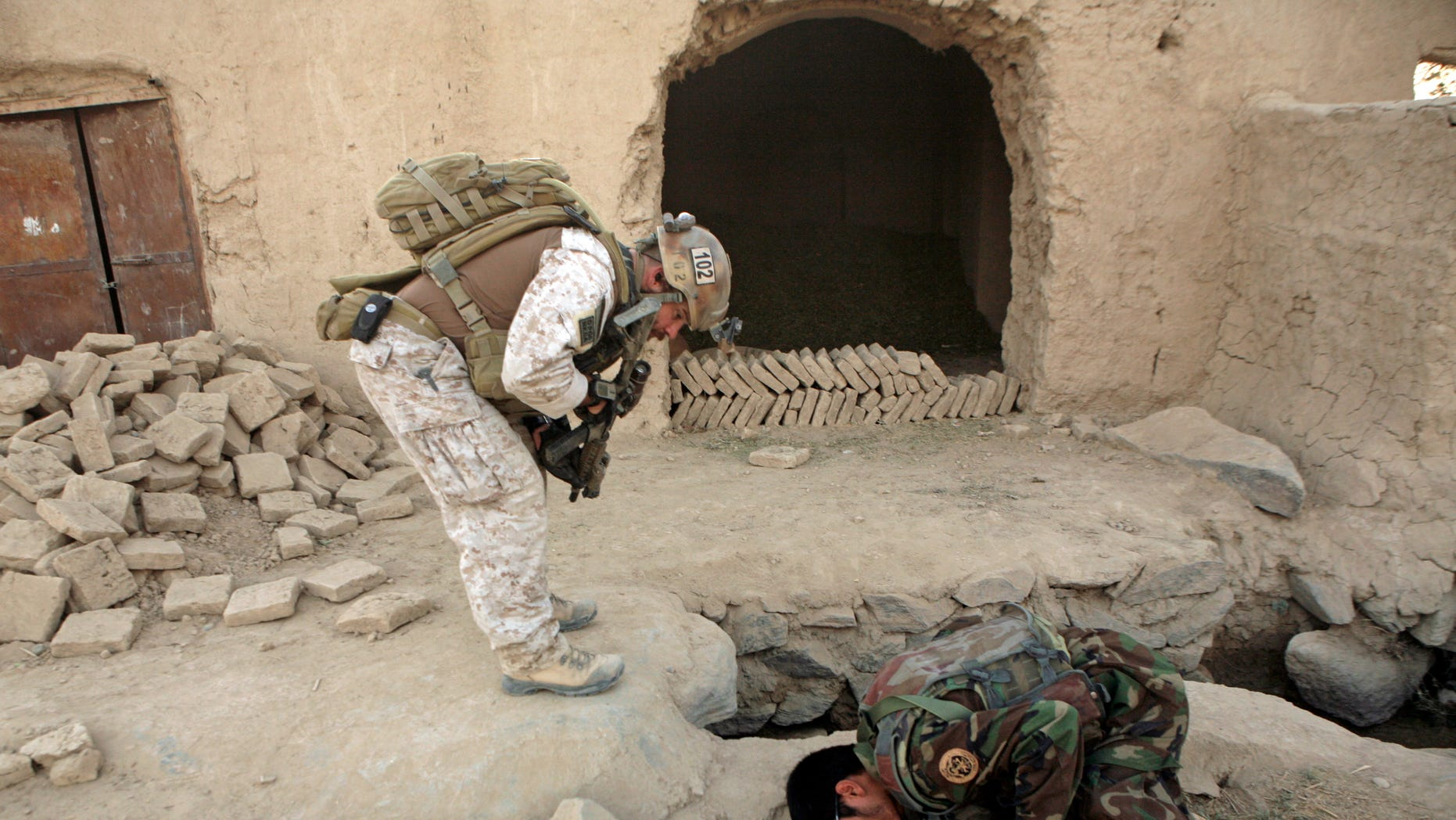 FILE - In this Saturday, Oct. 31, 2009 file photo, a member of U.S. special operations forces and an Afghan National Army soldier search for roadside bombs during a joint patrol in Shewan, a former Taliban stronghold in Afghanistan's Farah province.