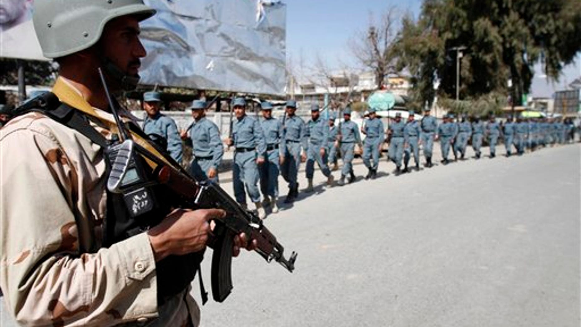 Feb. 25, 2012: Afghan policemen march towards an anti-U.S. demonstration in Mehterlam, Laghman province east of Kabul, Afghanistan.