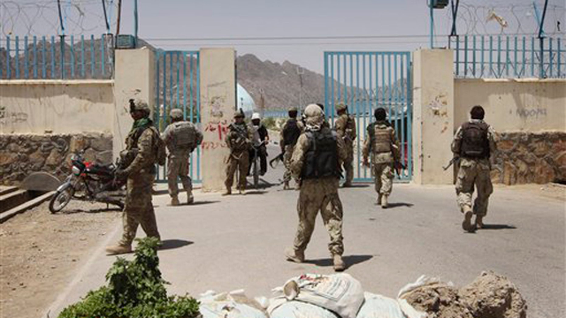 U.S. soldiers, left, and Afghan Police Commando forces, right, are seen at a university after a bomb blast in Kandahar, Afghanistan, on June 4.