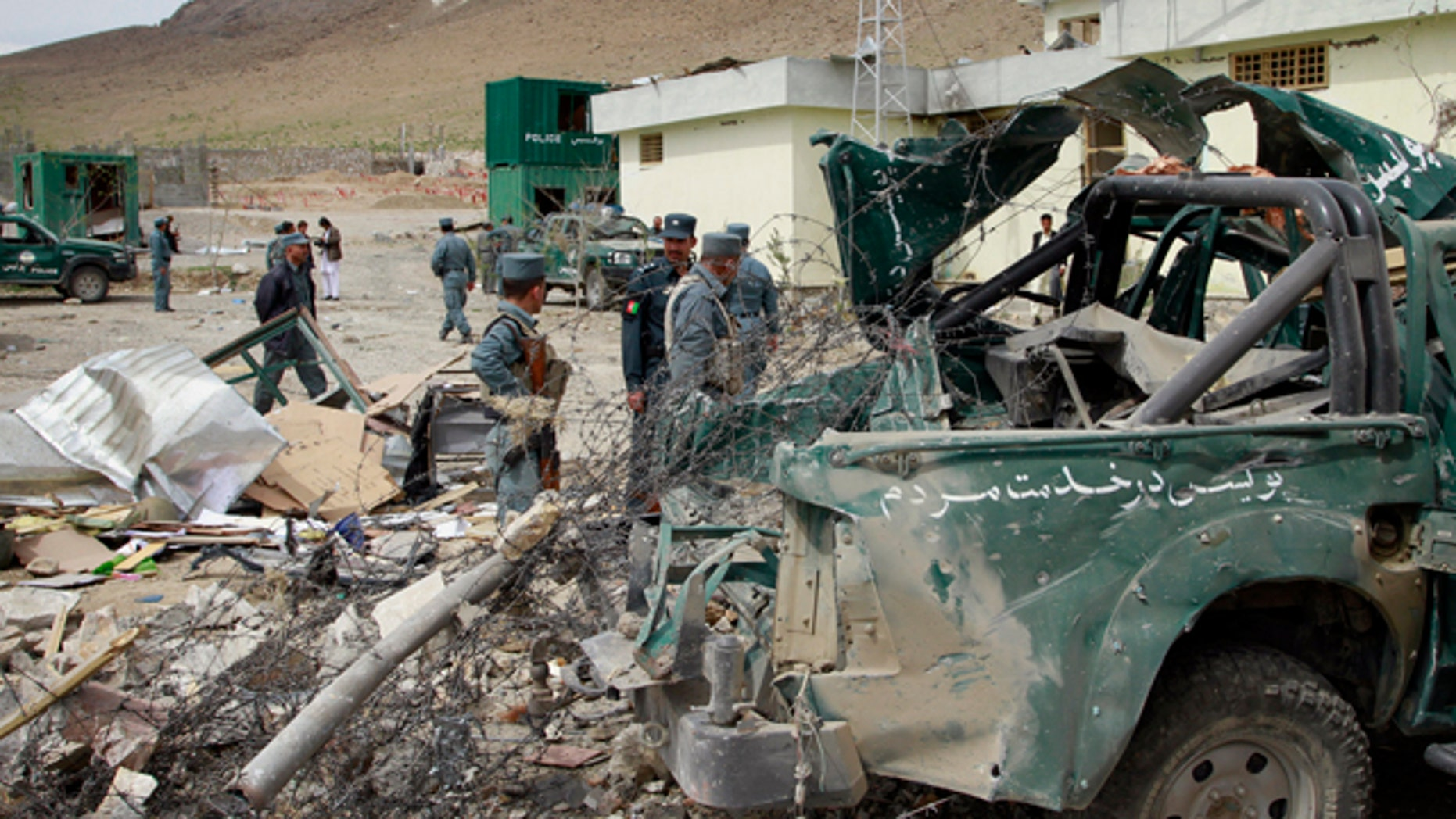 April 14: Afghan police men and officials stand close to a damaged police vehicle at the scene of a suicide car bomb explosion on the out skirts of Kabul, Afghanistan. A suicide car bomber detonated a truck of explosives covered in wood at a government compound in Musayi district, about 40 miles south of the Afghan capital, according Daud Amin, deputy police chief in Kabul. Six members of the Afghan national security forces were injured, he said. (AP)