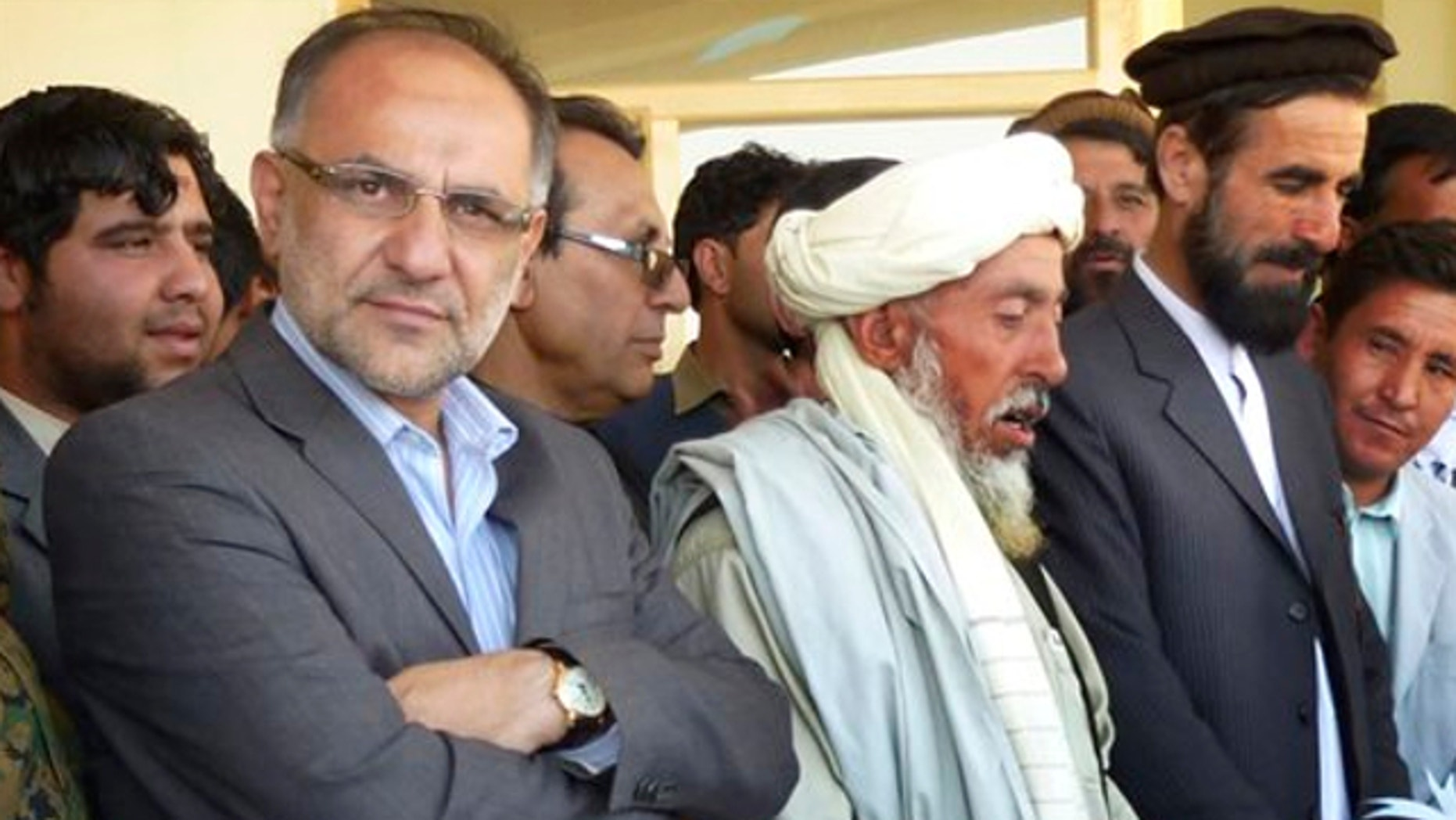 FILE: Oct. 12, 2013: Governor Arsallah Jamal, left, attends an opening ceremony of a school in Muhammad Agha, Logar province, Afghanistan. A bomb planted inside a mosque killed the governor of Afghanistan's eastern Logar province as he was delivering a speech Oct. 15.
