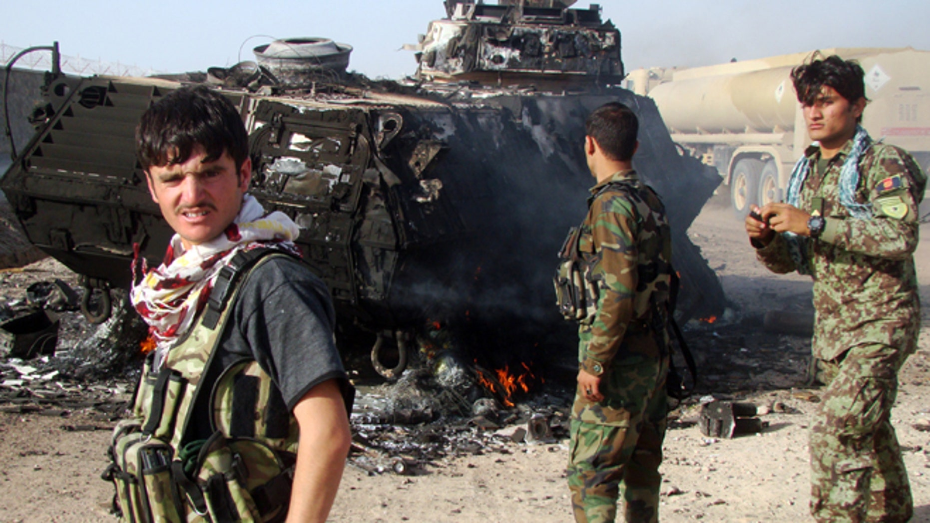 Oct. 18, 2014: In this file photo, Afghan security forces inspect the site of a suicide attack, targeting an Afghanistan's National Army convoy on the outskirts of Lashkar Gah, the capital of Helmand province, Afghanistan.