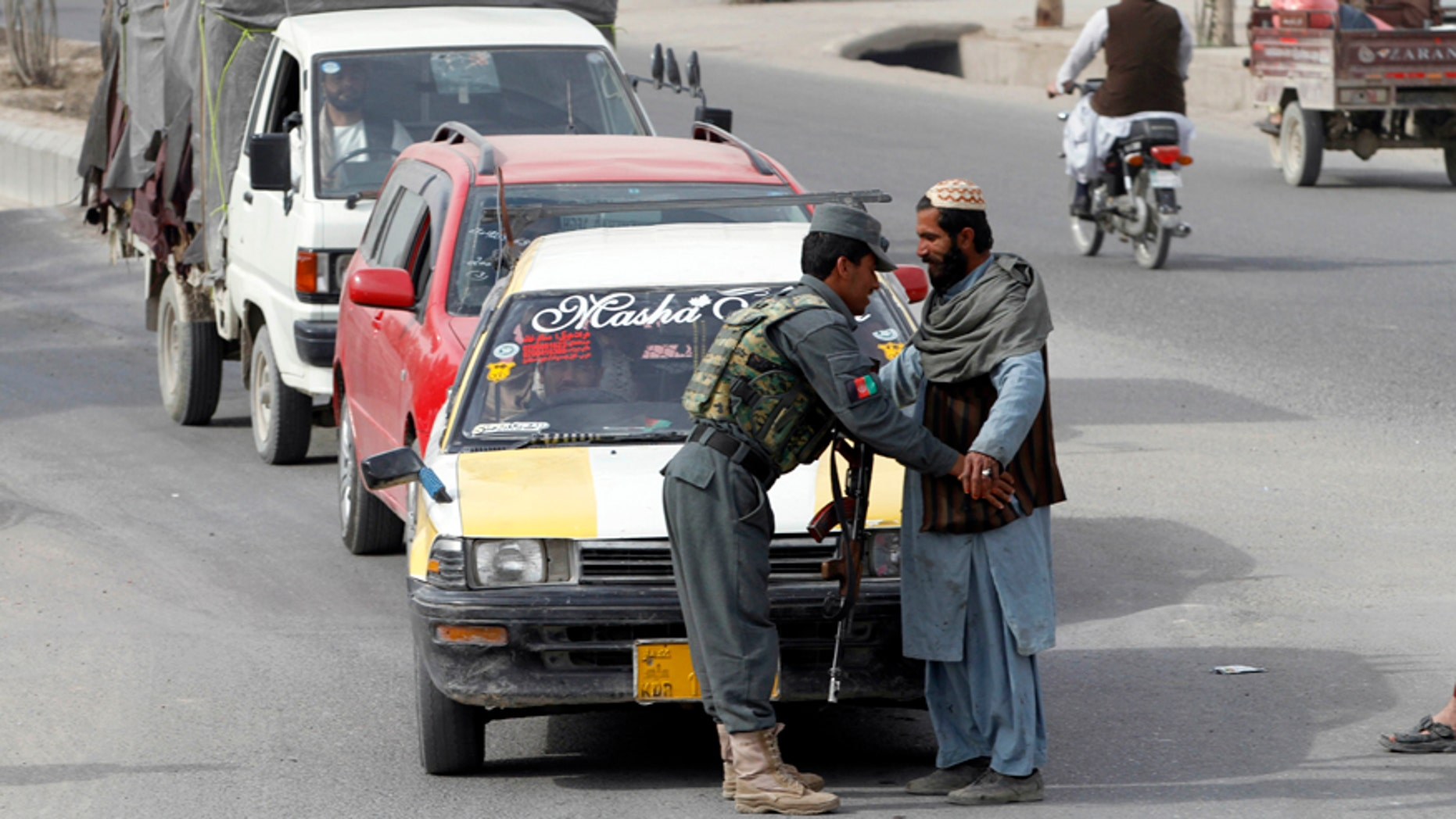 Jan. 26, 2016: An Afghan policeman searches a passenger at a checkpoint in Kandahar, Afghanistan.