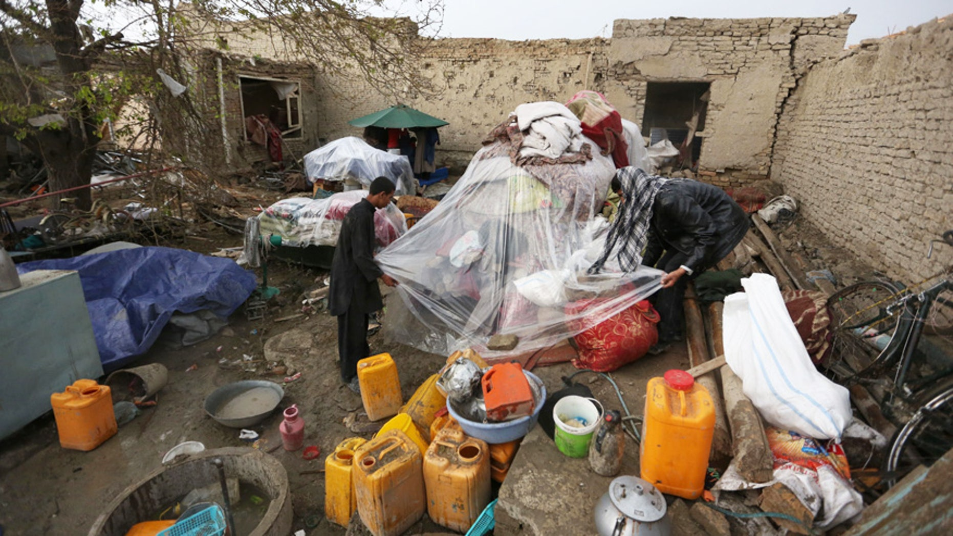 April 20, 2016: Afghan boys inspect the remains of their belongings from a damaged house after a Taliban-claimed deadly suicide attack in Kabul, Afghanistan.