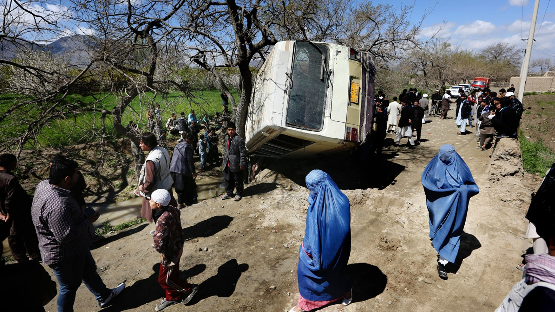 April 11, 2016: Afghan women walk past a damaged bus after a roadside bomb explosion on the outskirts of Kabul.
