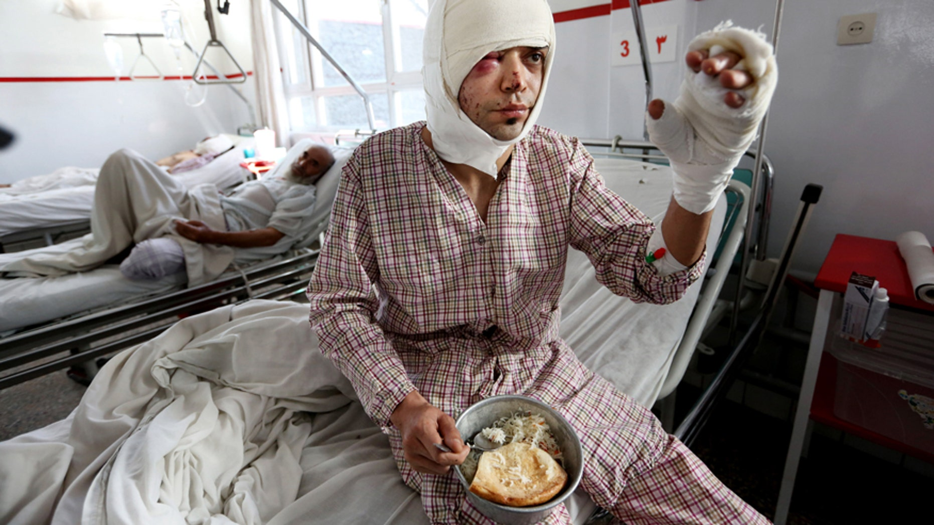 Jan. 21, 2016: An injured victim from Wednesday's suicide attack near the Russian Embassy, tries to eat at a hospital in Kabul, Afghanistan.