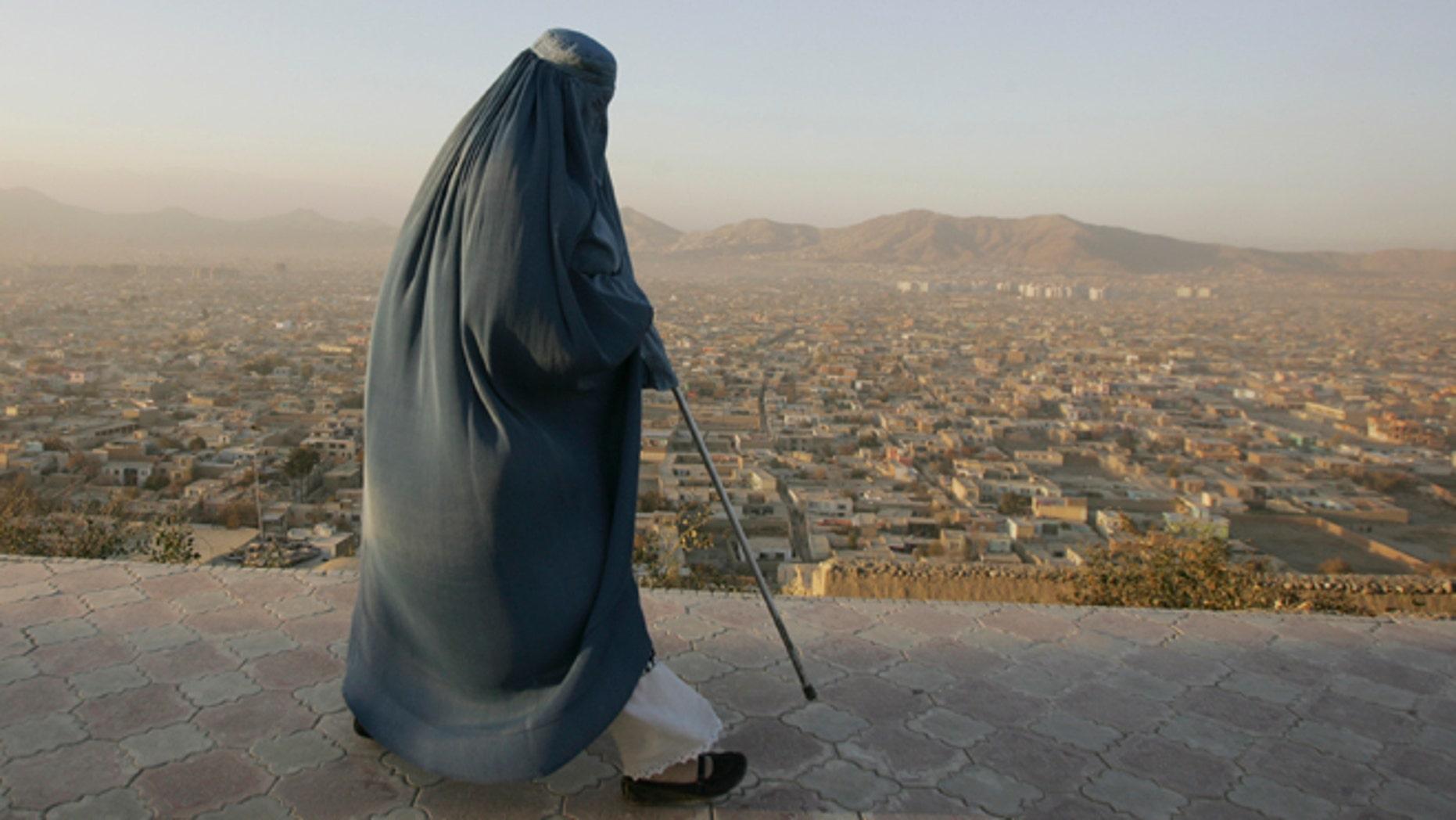 Nov. 11, 2012: An Afghan woman walks on a hill overlooking Kabul, Afghanistan.
