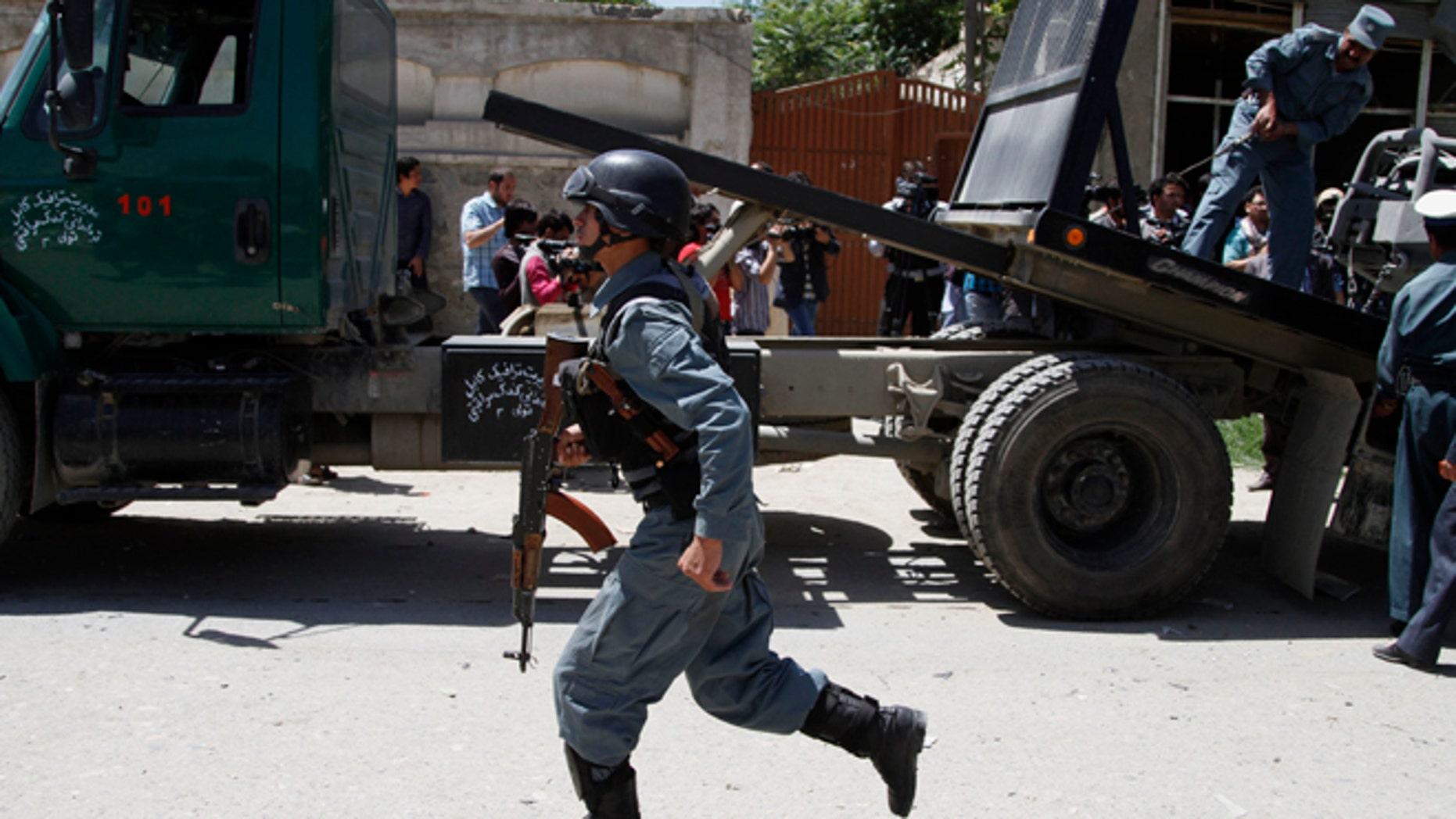 June, 18, 2013: An Afghan police officer runs at the site of a blast near the Afghan Independent Human Rights Commission in Kabul, Afghanistan. The large bomb exploded in the Afghan capital on Tuesday as the international military coalition hands over responsibility for fighting the Taliban insurgency to the nascent national army and police they have been training.