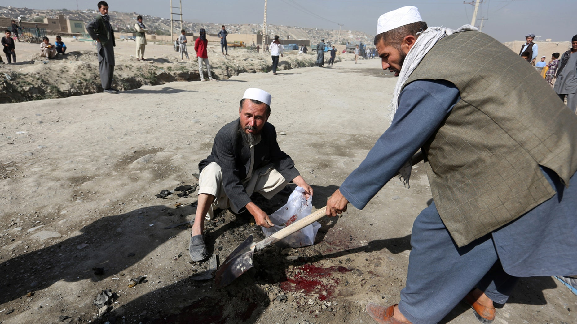 Aug. 20, 2016: Afghan men clean the site of a bomb blast on the outskirts of Kabul. A soldier was killed early Saturday by a sticky bomb placed on his vehicle, Kabul police said.