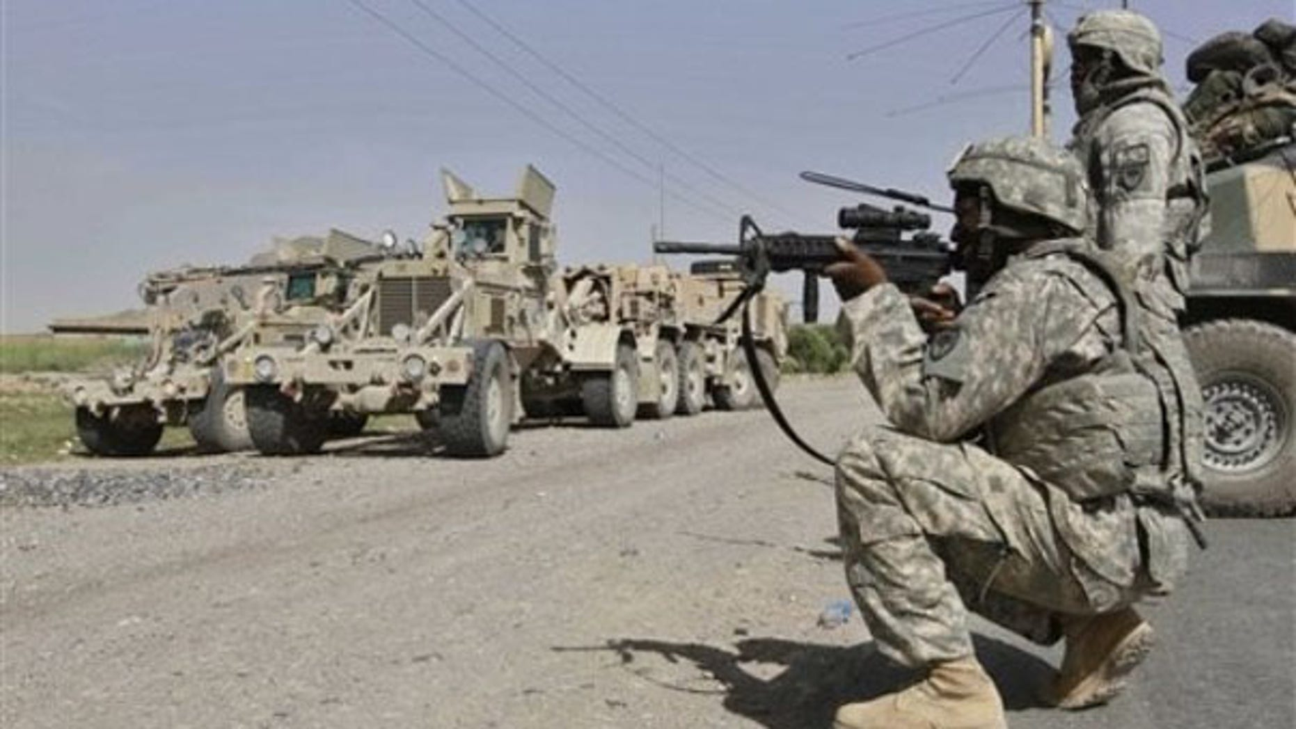 Thursday: A U.S. soldier looks at an approaching man through the sights of his assault rifle as the soldiers provide security during investigations at a site of suicide attack in Kandahar, Afghanistan. (AP Photo)