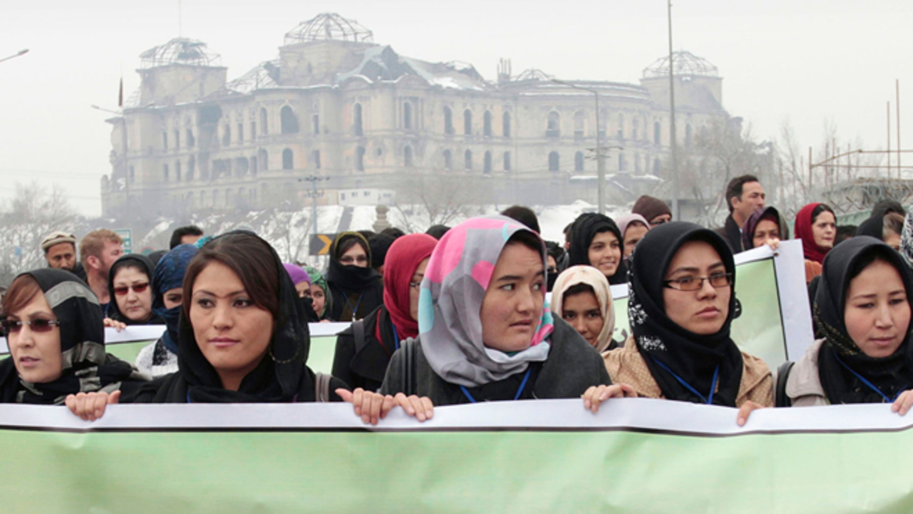 Feb. 14, 2013: Afghan women carry a banner during a march calling for end of violence against women, in Kabul, with the Darul Aman palace seen in the background, Afghanistan.