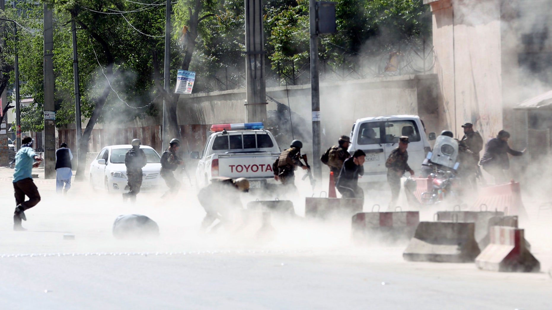 Afghan security forces run from a second suicide attack in Kabul Monday.