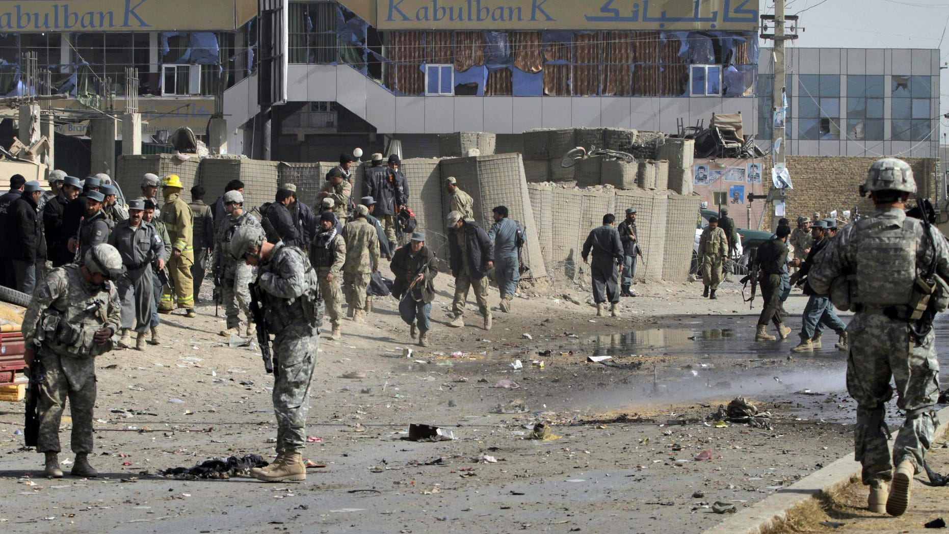 Dec. 27: U.S soldiers and Afghan policemen are seen at the scene of a suicide attack in Kandahar south of Kabul, Afghanistan. On Dec. 28 a U.S. military commander says it's 'naive' to think there's a practical way to seal Afghanistan's vast border with Pakistan and stop all Taliban fighters from slipping through.