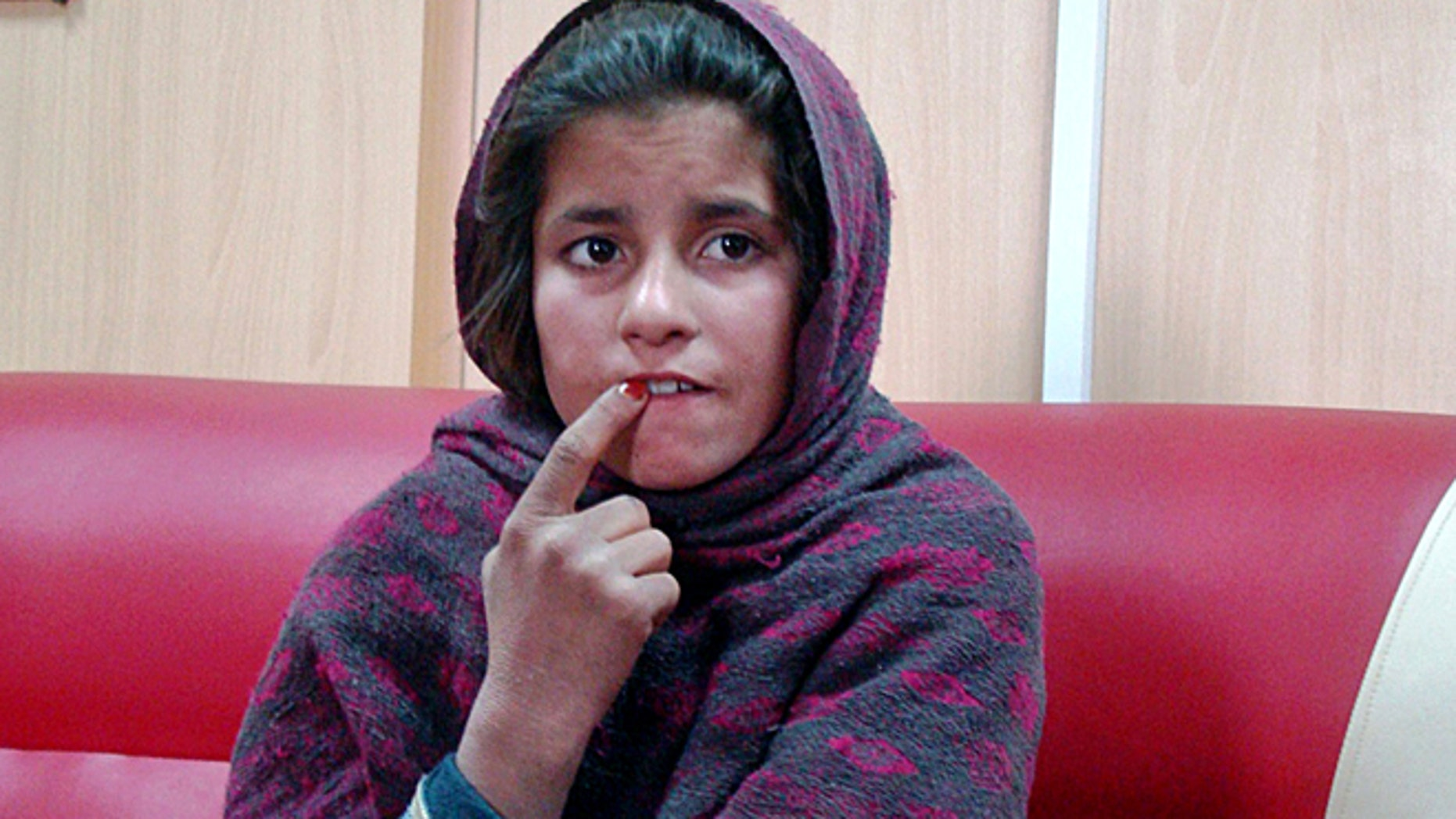 Jan. 6, 2014: In this photo, an Afghan girl named Spozhmai is held in a border police station in the Khan Neshin district in the southeastern part of Helmand province, Afghanistan.