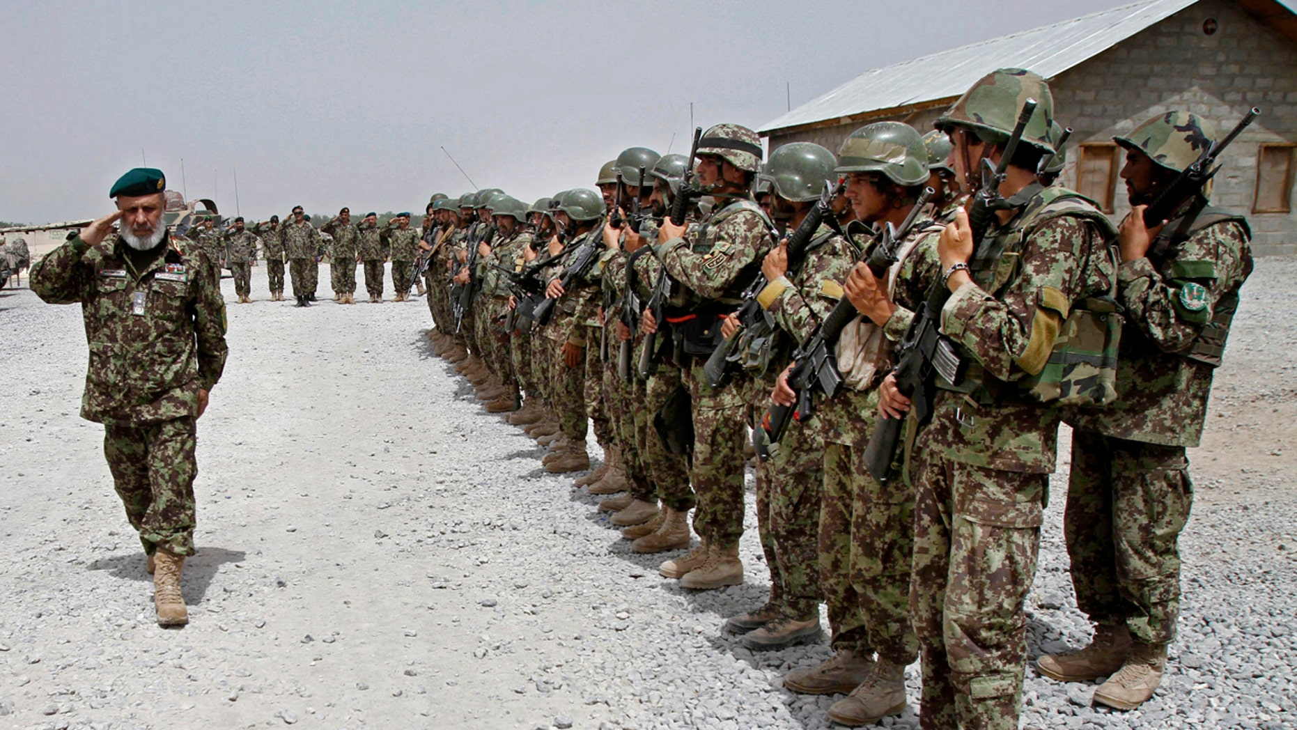 In this Thursday, June 13, 2013 file photo, Afghan National Army soldiers stand in position, in the Sangin district of Kandahar province, southern Afghanistan.