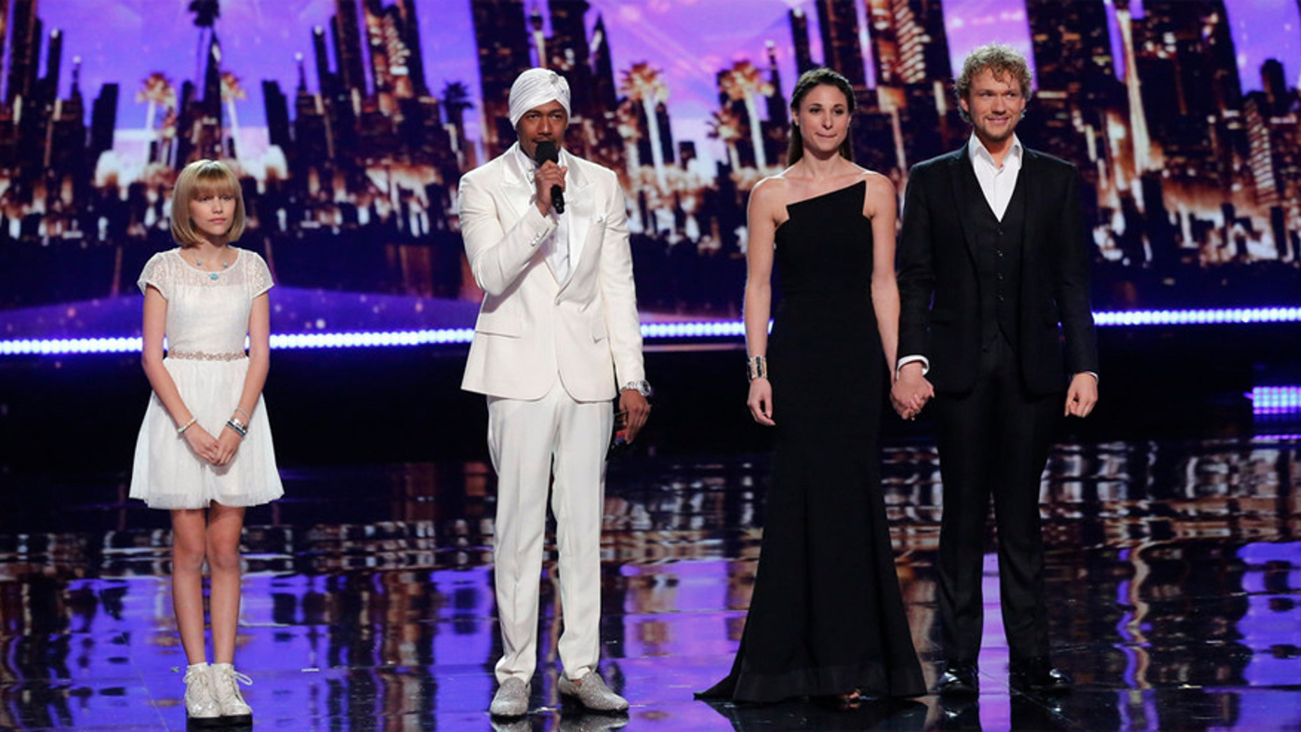 """Grace VanderWaal (left) and The Clairvoyants (right) wait to hear host Nick Cannon (center) announce the """"America's Got Talent"""" winner."""