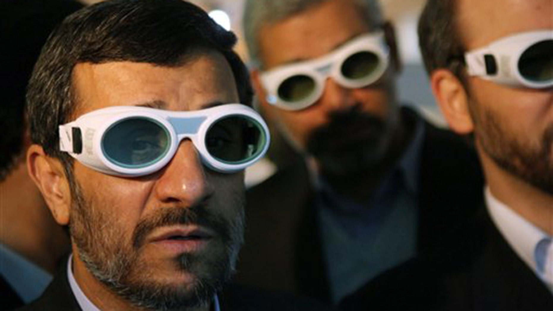 In this Feb. 7 file photo, Iranian President Mahmoud Ahmadinejad wears eye protection goggles as he visits an exhibition of Iran's laser science in Tehran.